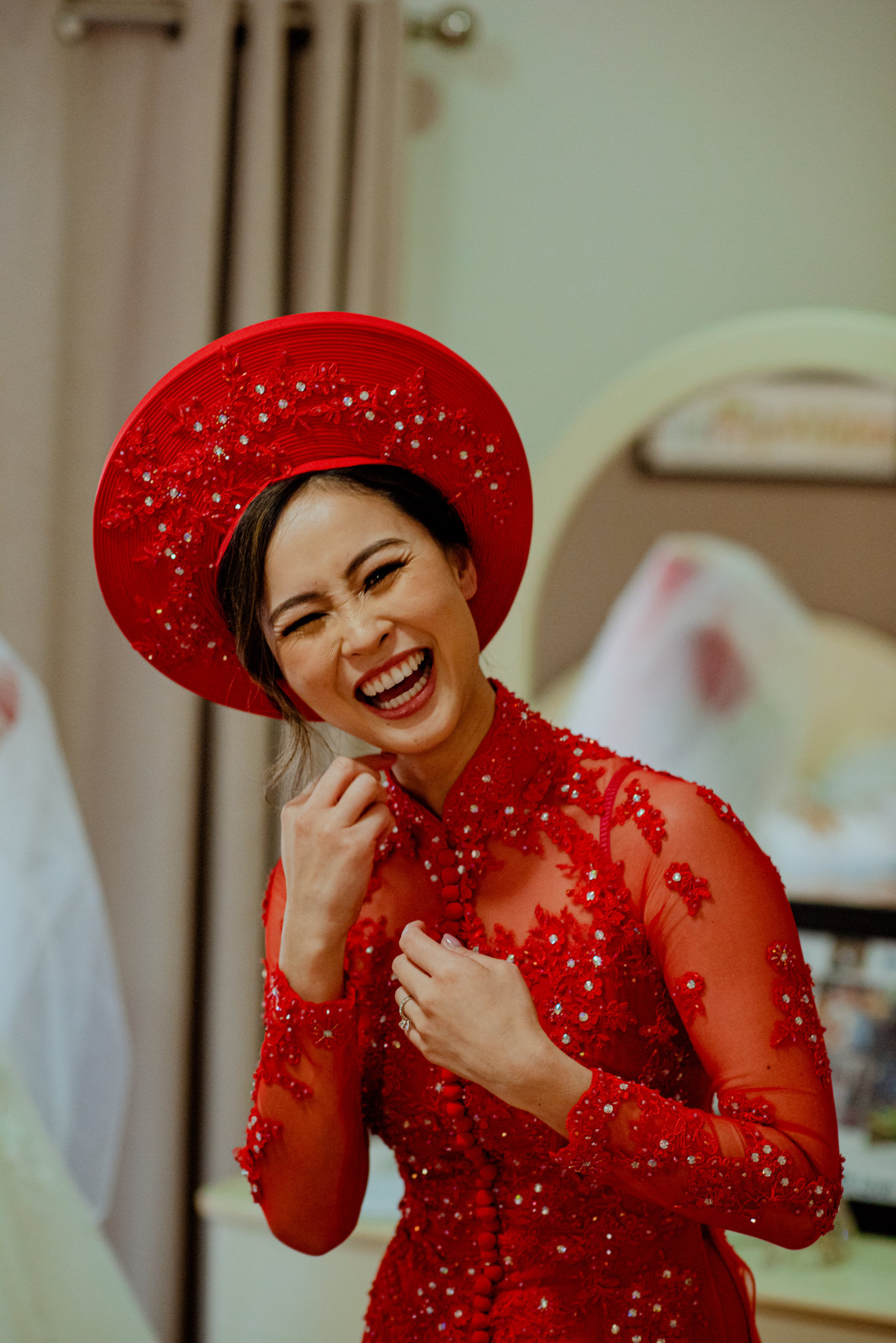 Vietnamese woman laughs as she wears traditional red dress and hat