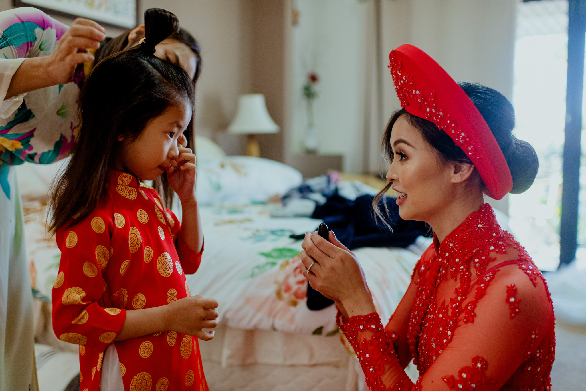 Asian lady in traditional Vietnamese dress helps young girl get dressed
