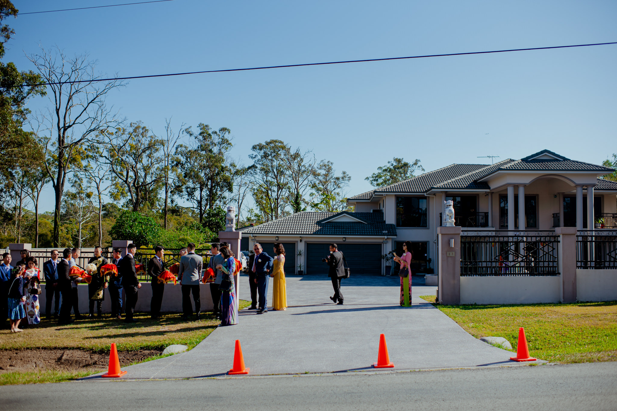 People in formal clothing line up in front of a large house with traffic cones in front