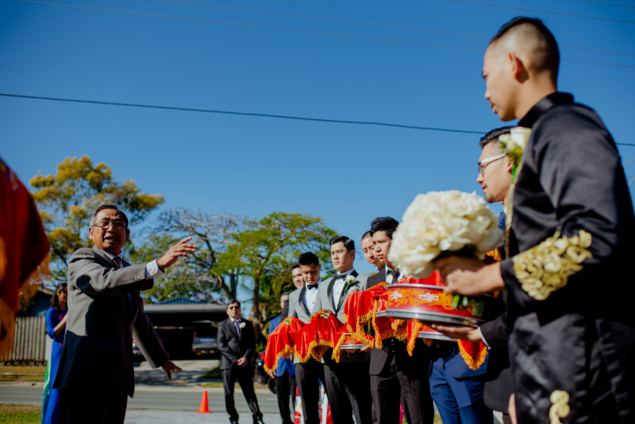 Men holding traditional Vietnamese wedding gifts line up together