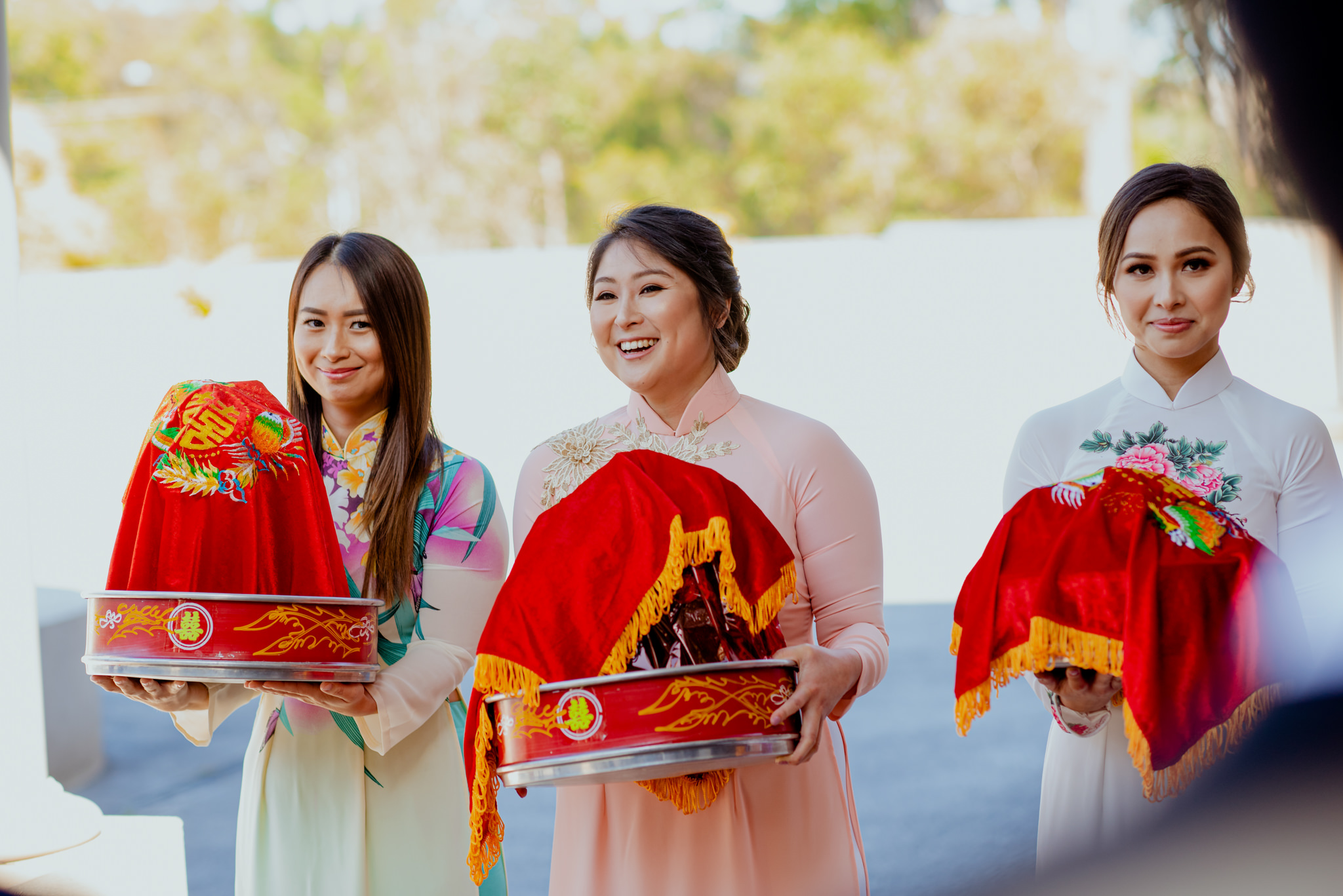 Vietnamese women laugh as they hold large red presents and wear traditional Vietnamese clothes