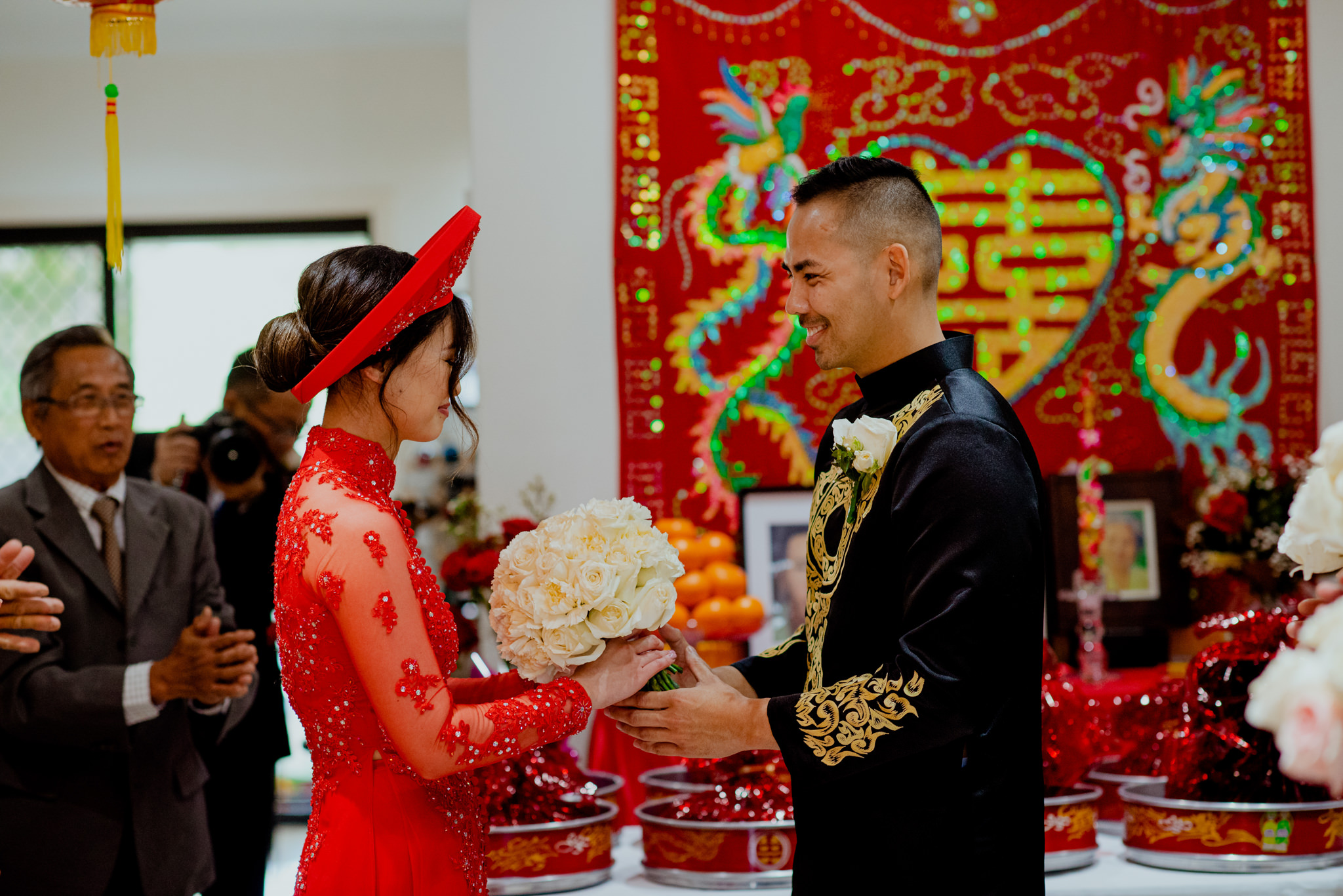 A Vietnamese bride and groom meet together and smile wearing traditional Vietnamese wedding clothes