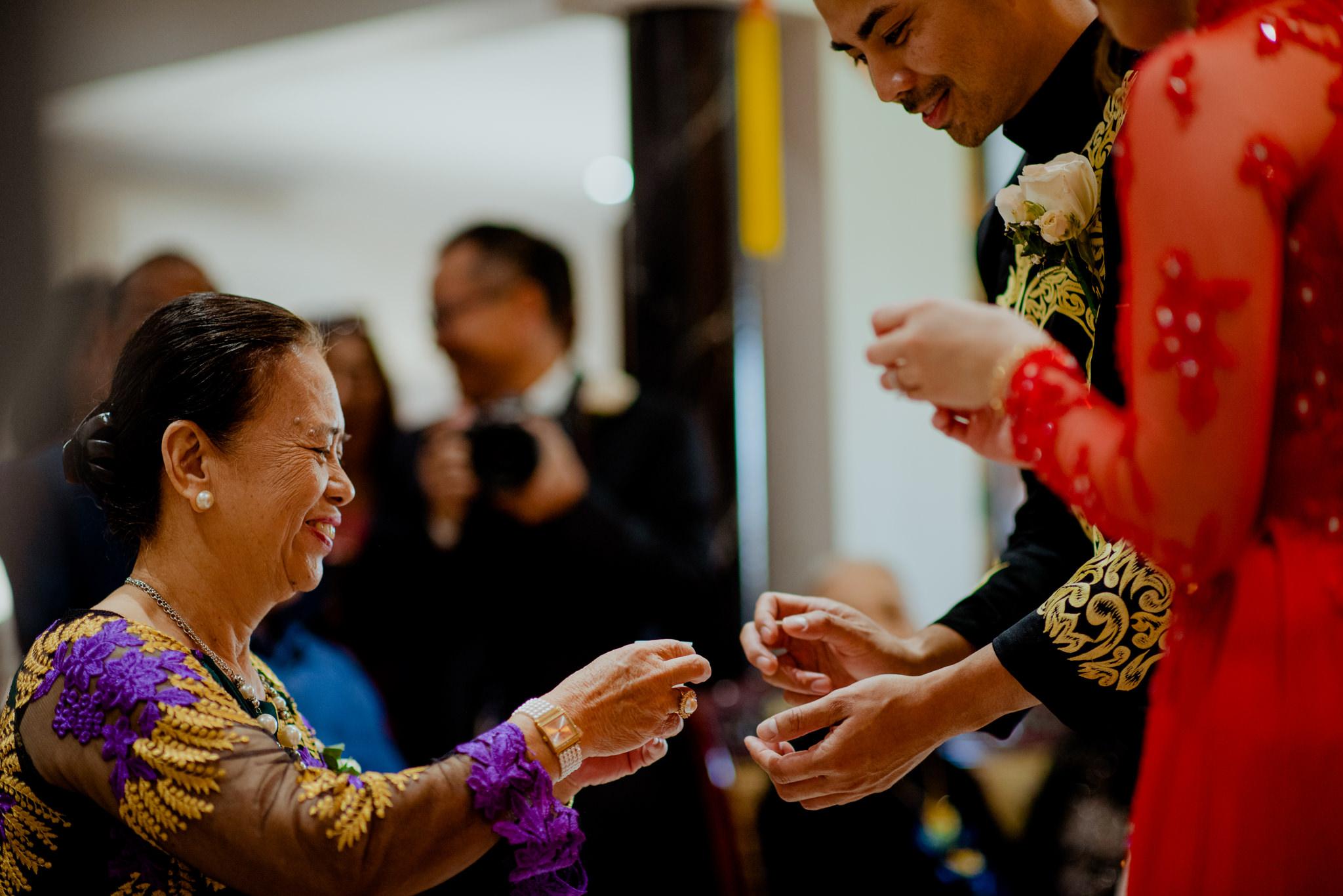 Man serves tea to an elderly woman during an Asian tea ceremony