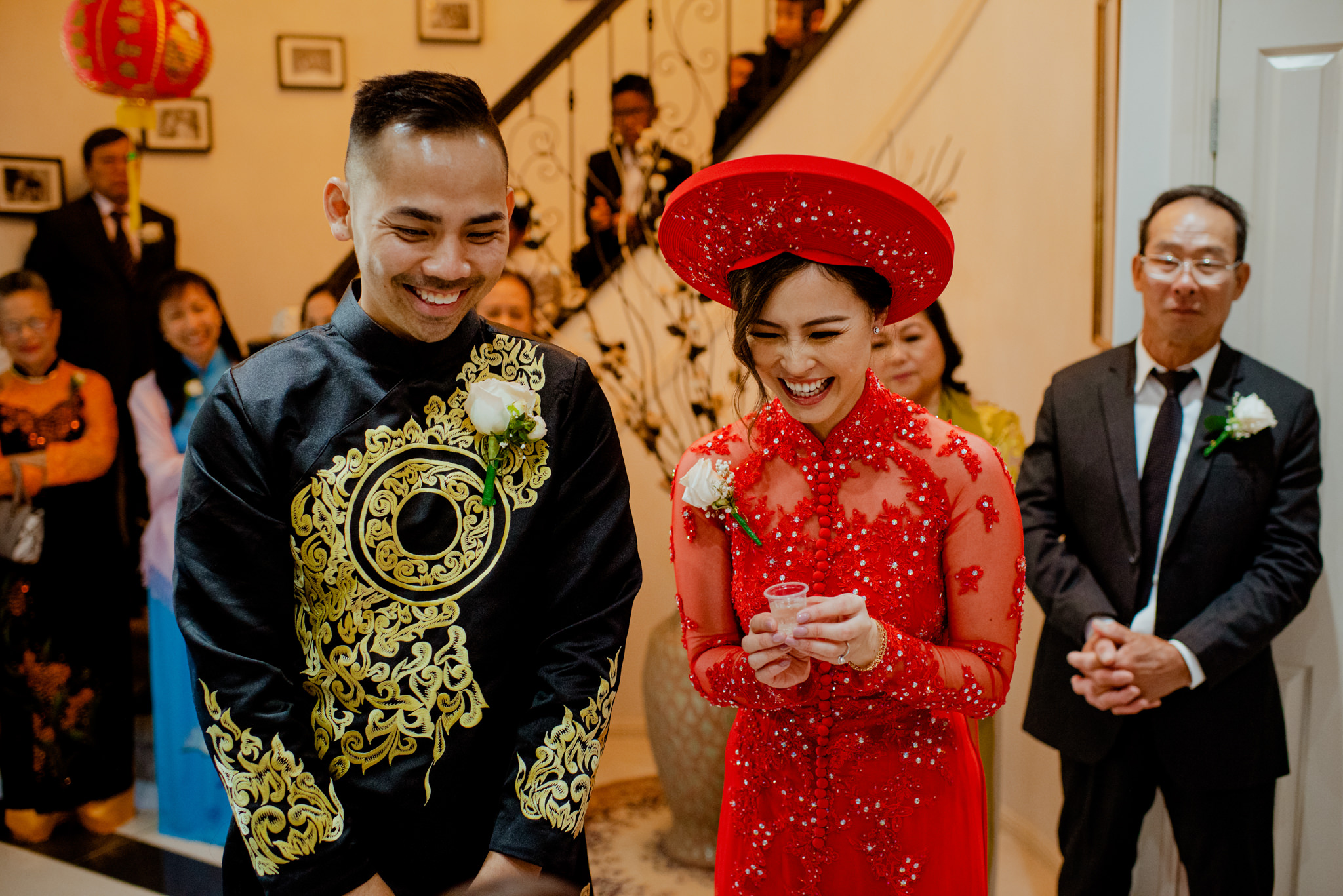 Vietnamese bride and groom laugh as they serve tea during an Asian tea ceremony