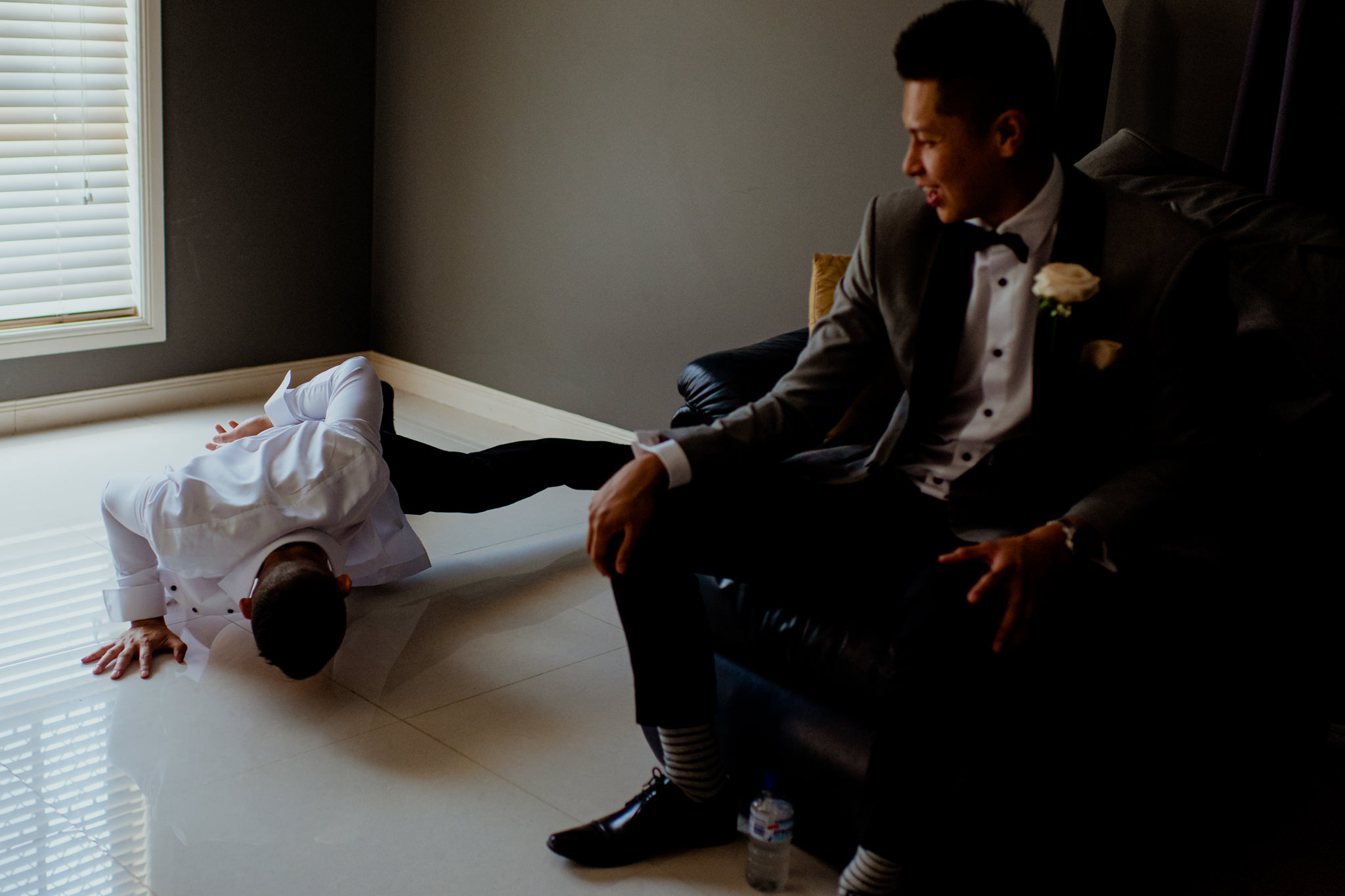 A man wearing a formal shirt does one handed pushups next to a man wearing a suit sitting on a chair