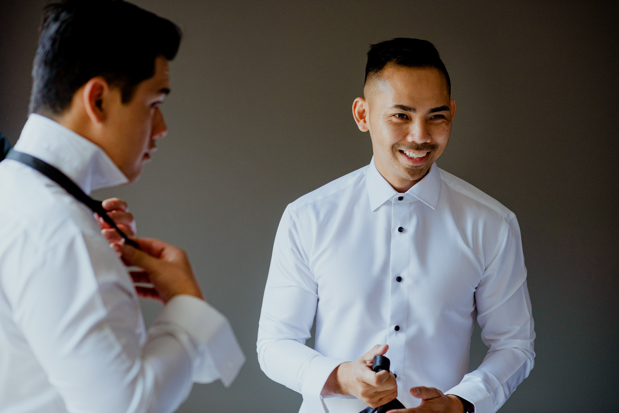 Two asian men laugh as they get dressed into formal clothes