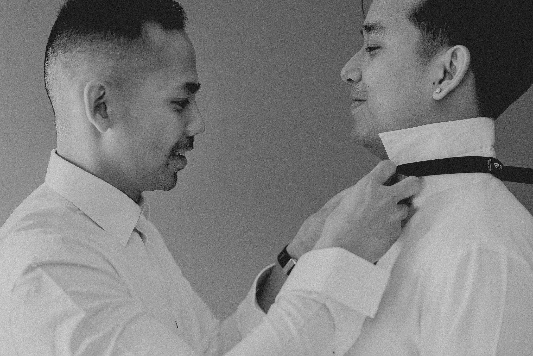 One man helps another man tie his bow-tie