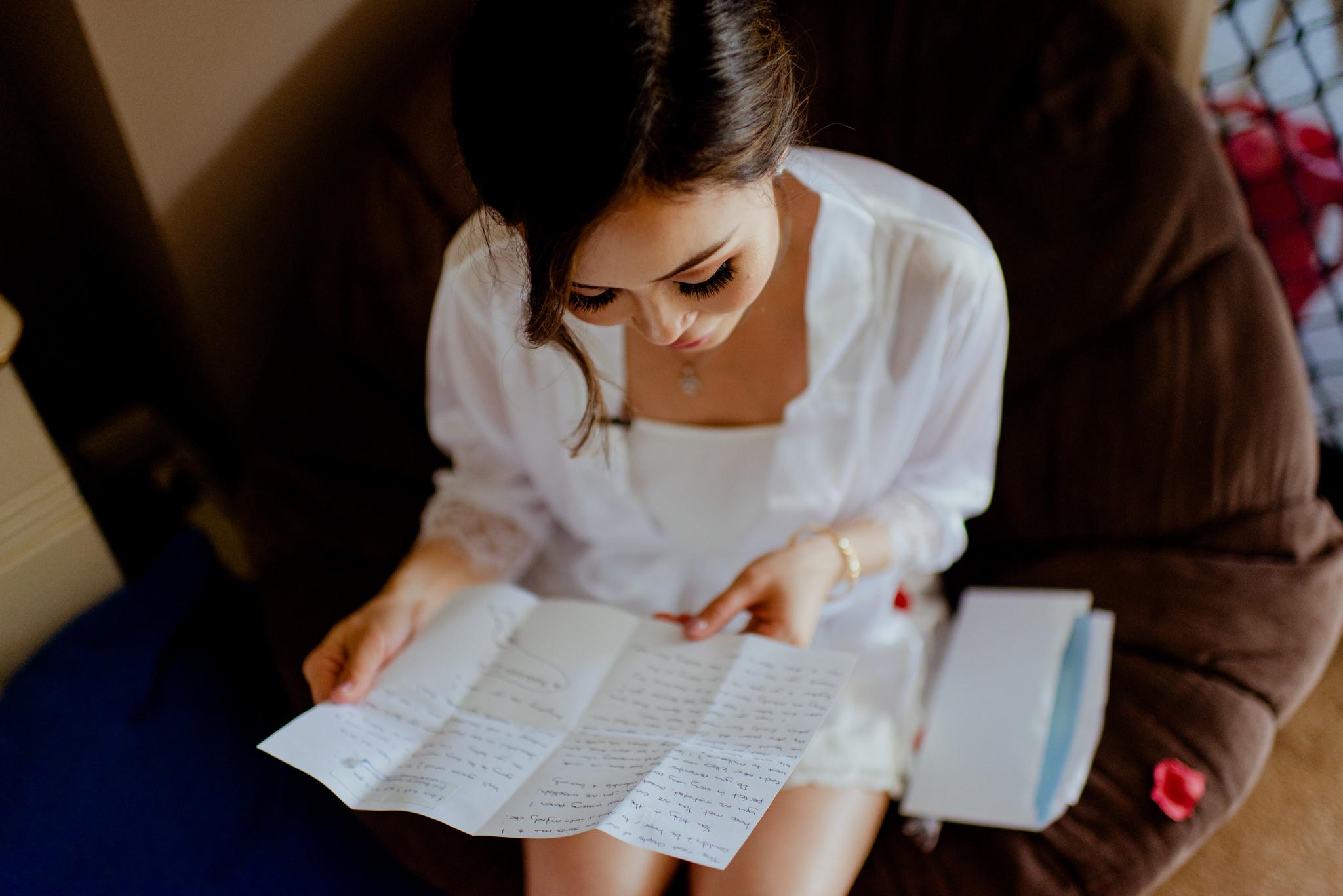 An asian woman reads a hand-written note on a chair