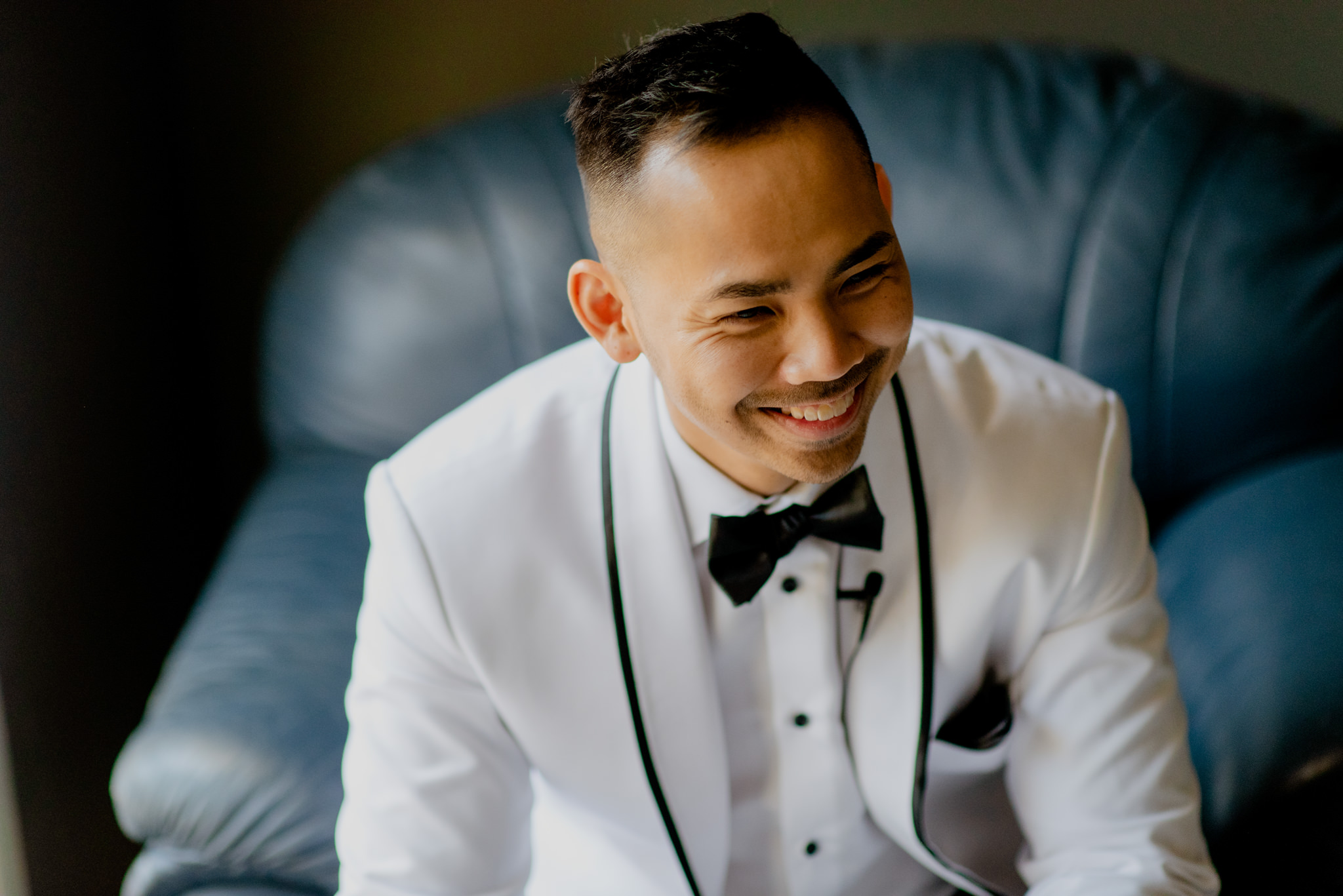 An asian man in a white tuxedo sitting on a chair laughs