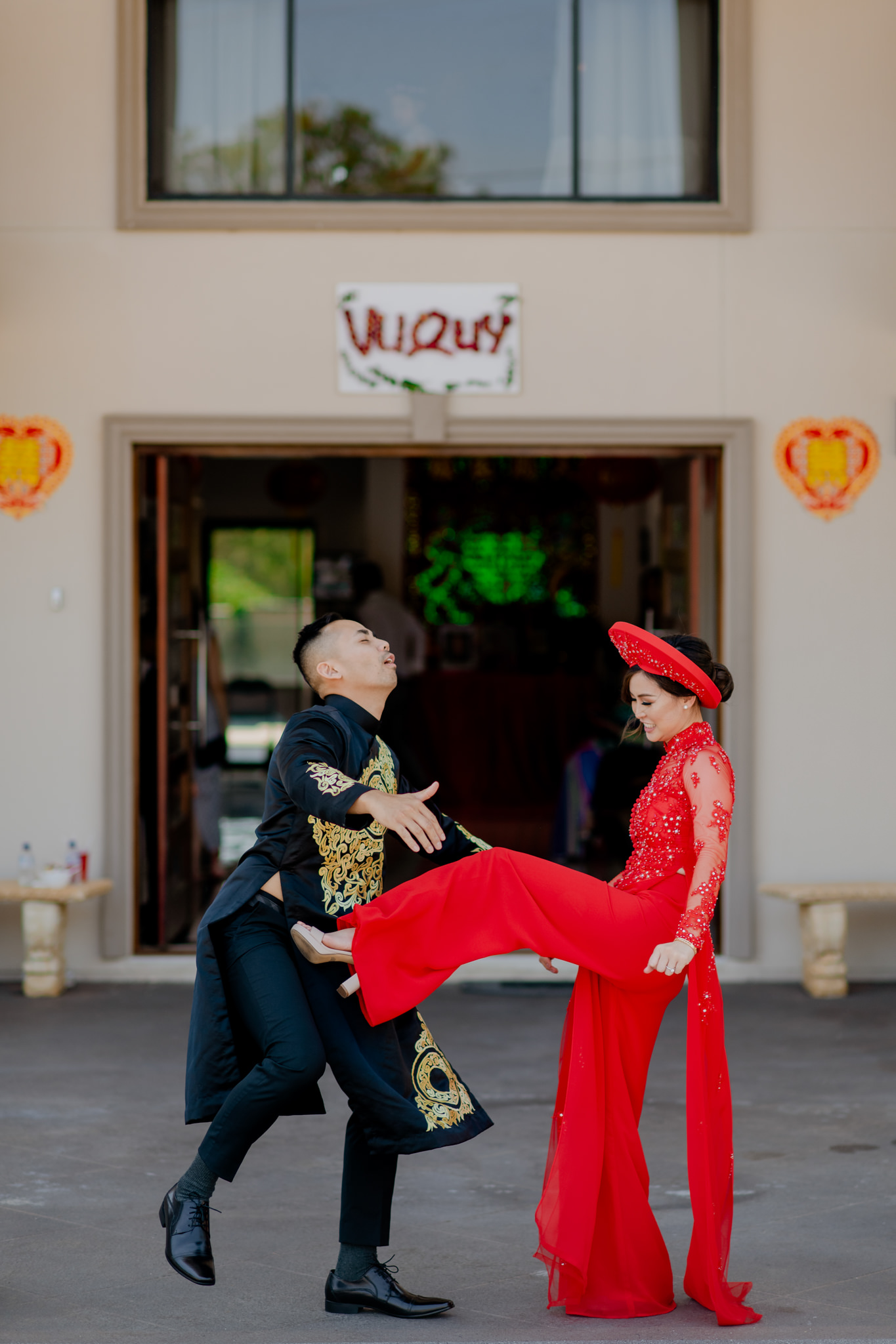 A couple wearing traditional Vietnamese clothing playfully fight in front of a house