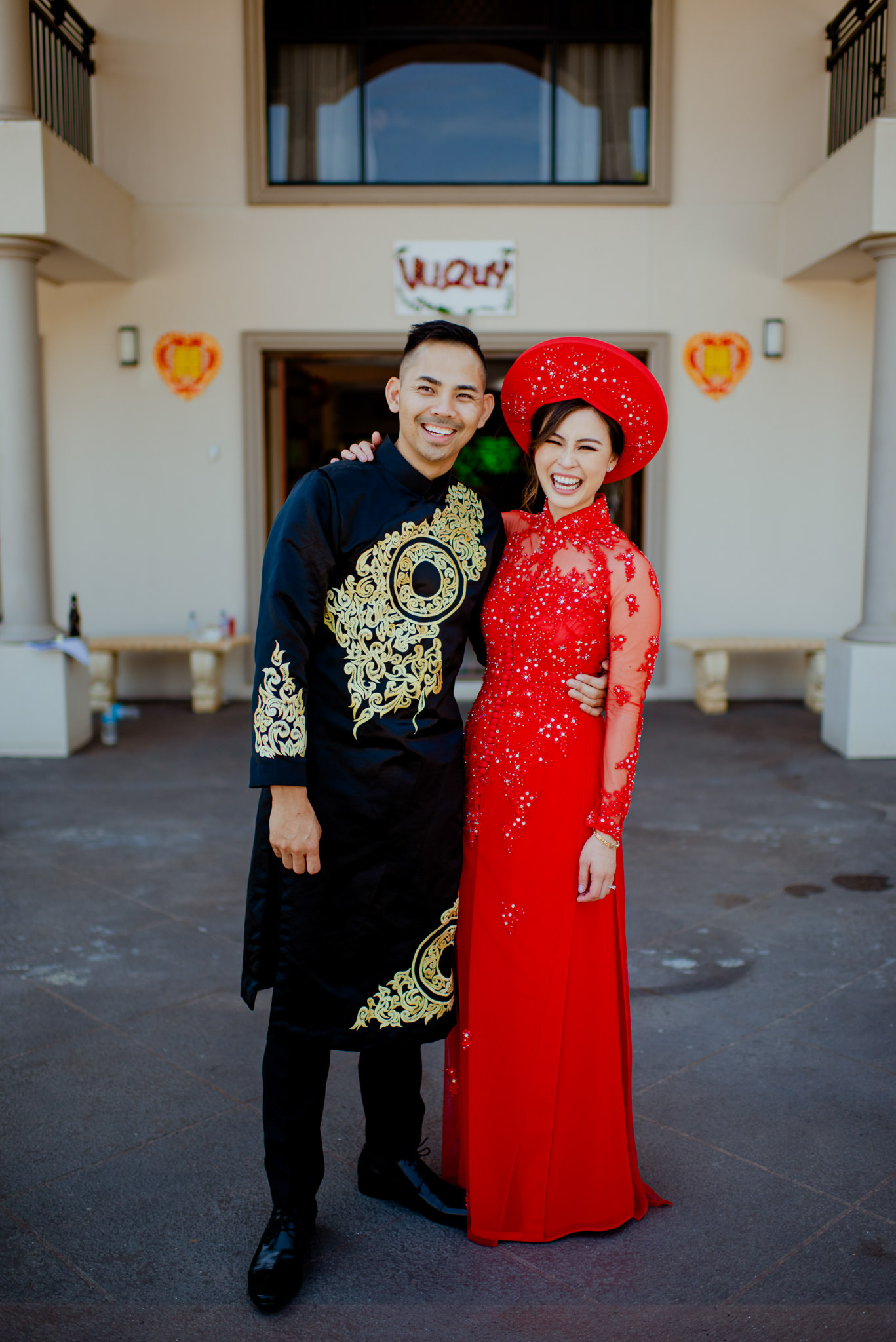 A couple wearing traditional Vietnamese clothing laugh and hug