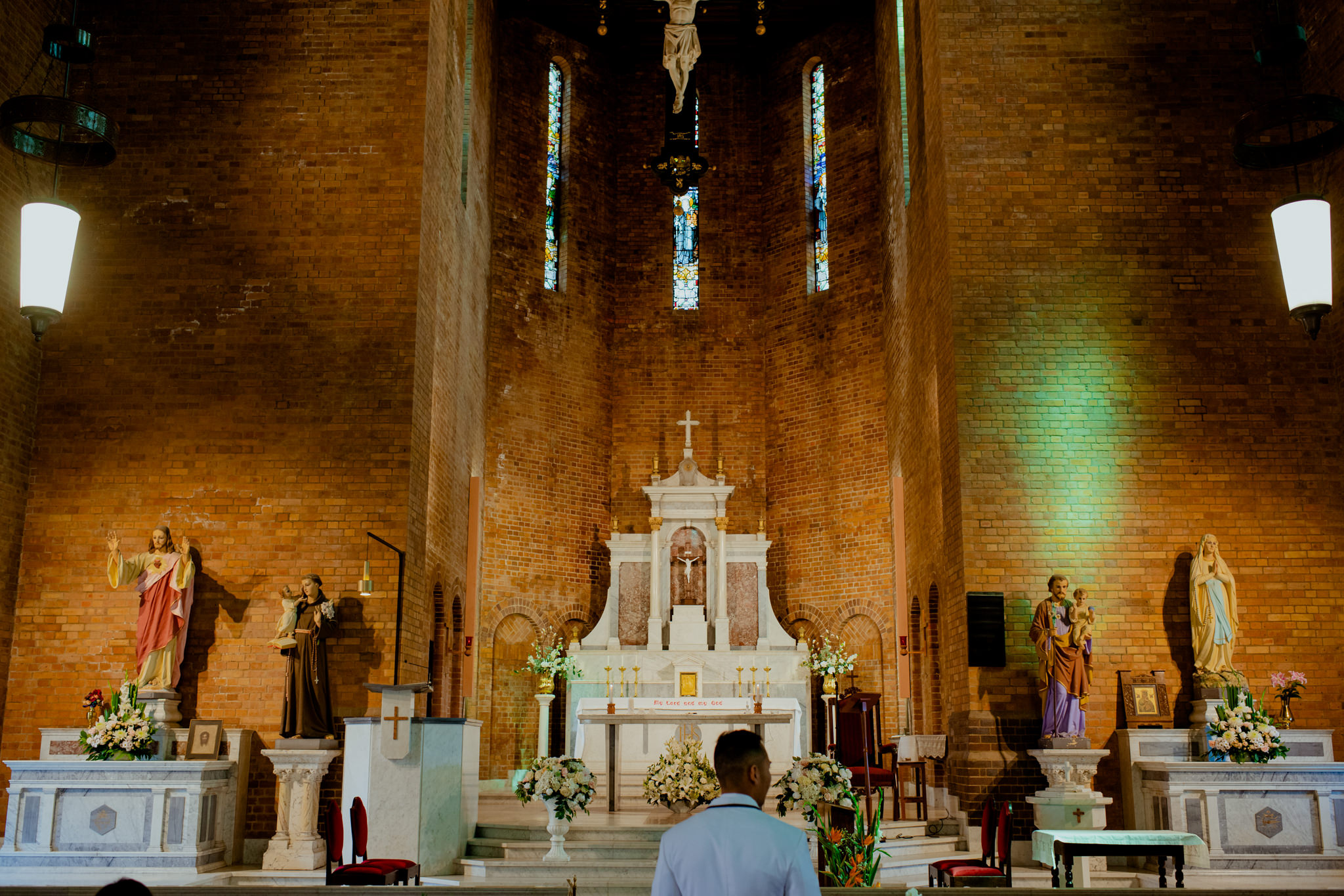 The interior of a tall and large brick Catholic church