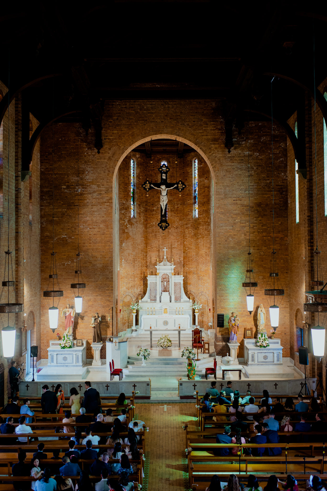 The interior of a tall and large brick Catholic church filled with wedding guests
