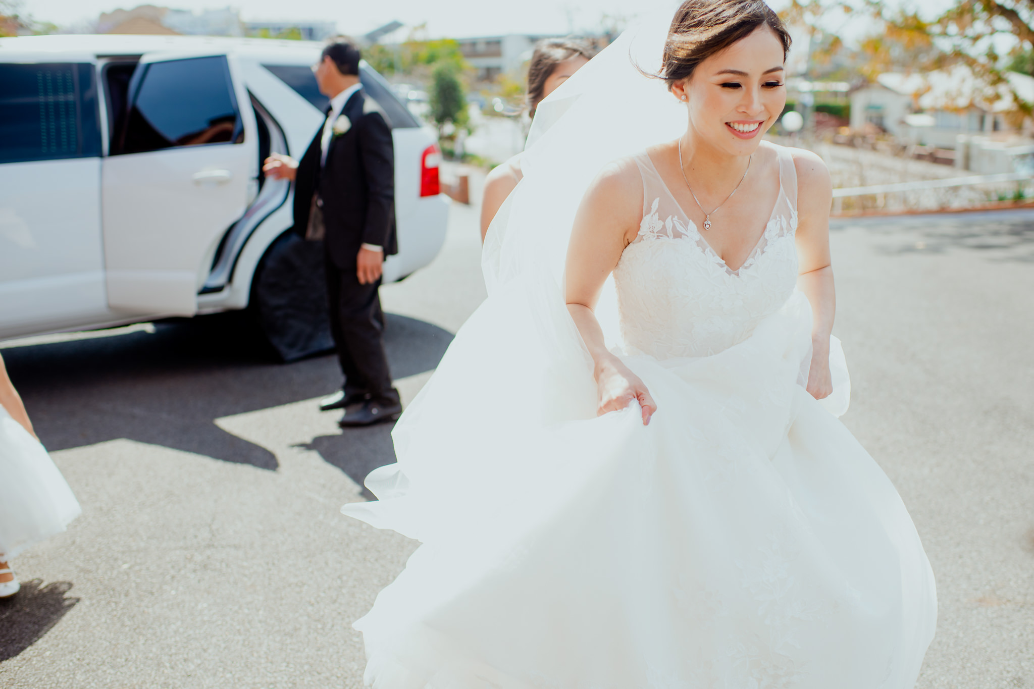 A bride in her wedding dress excitedly walks away from her car