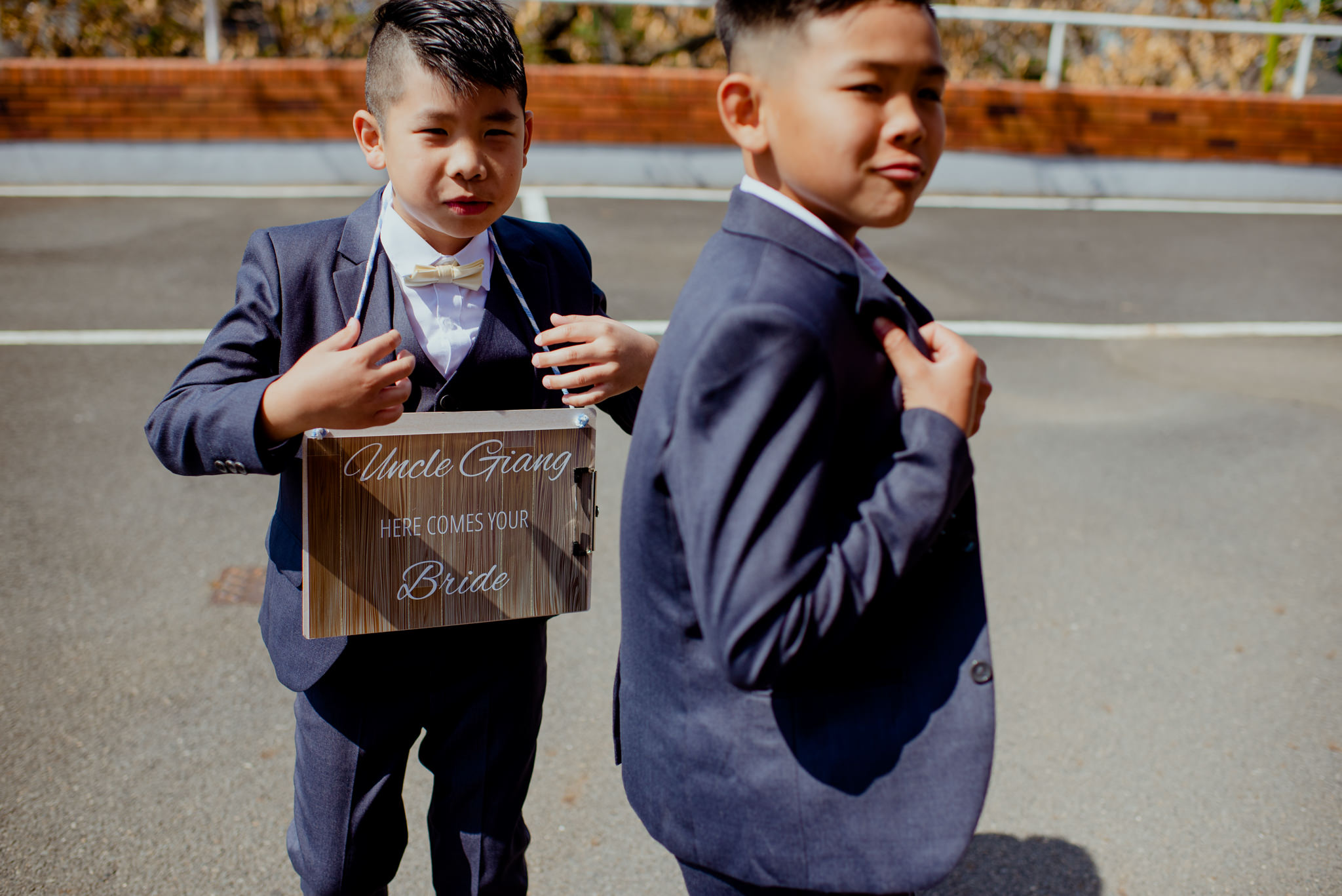 Two page boys in suits pose for a photo