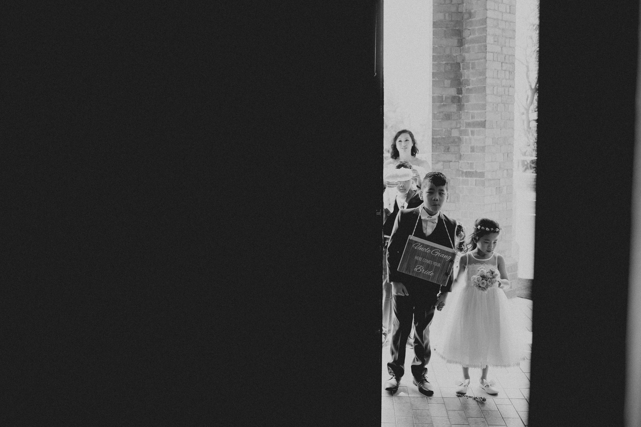 A page boy and flower girl wait outside the church before they enter a wedding ceremony