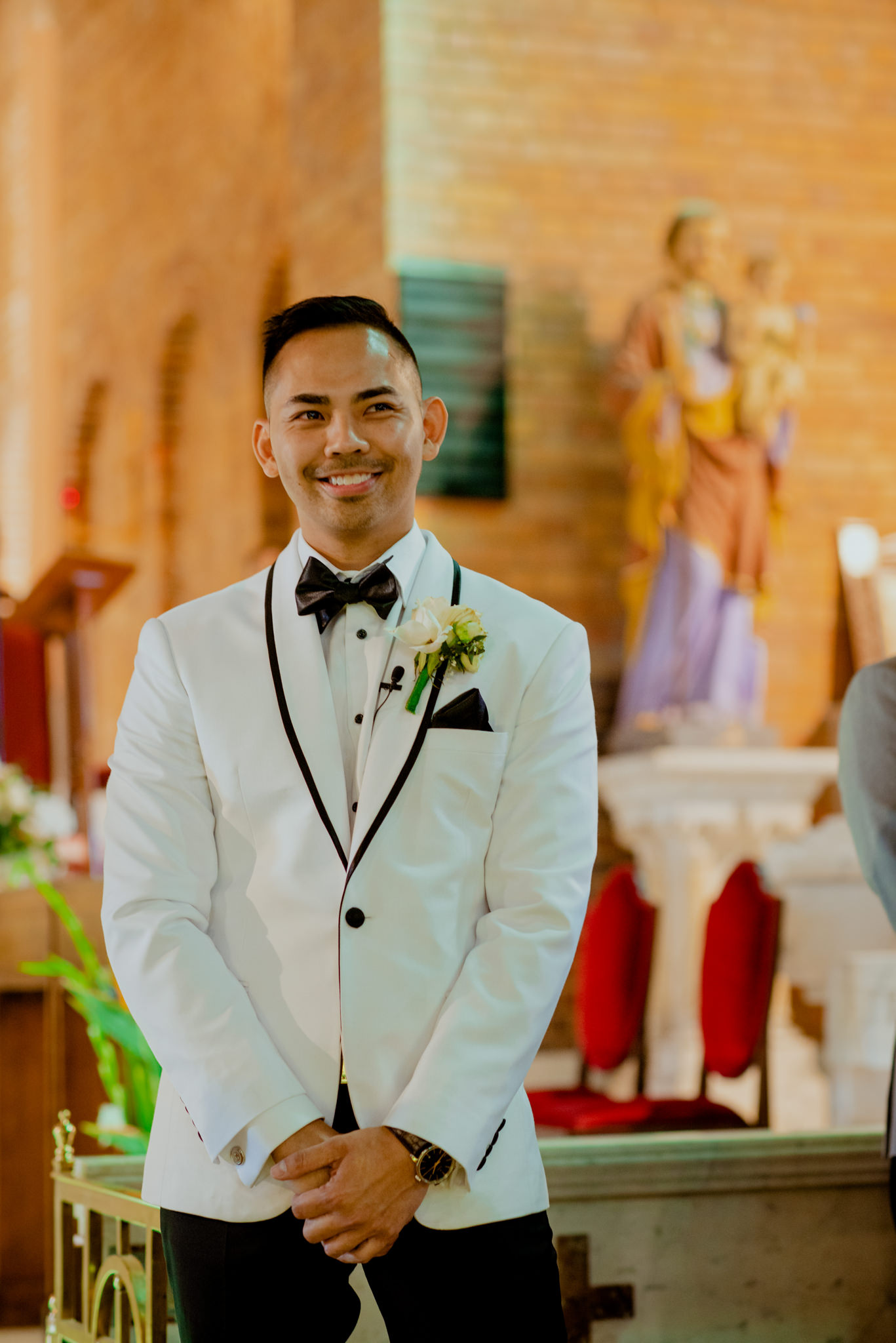 Groom nervously smiles as he stands and waits for his bride to arrive