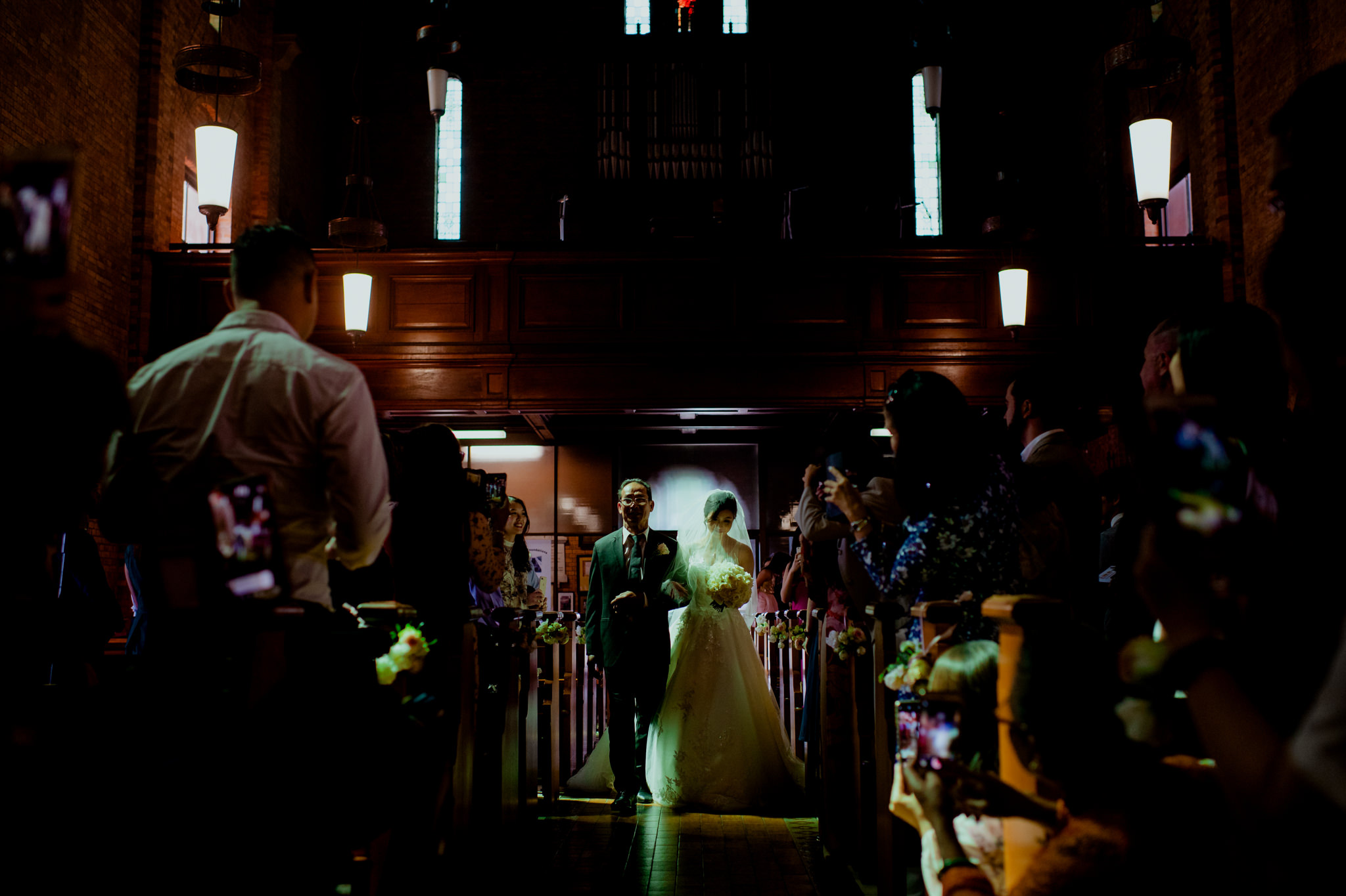 Bride and her father walk down the aisle of a dark church but the bride is illuminated by a green spotlight
