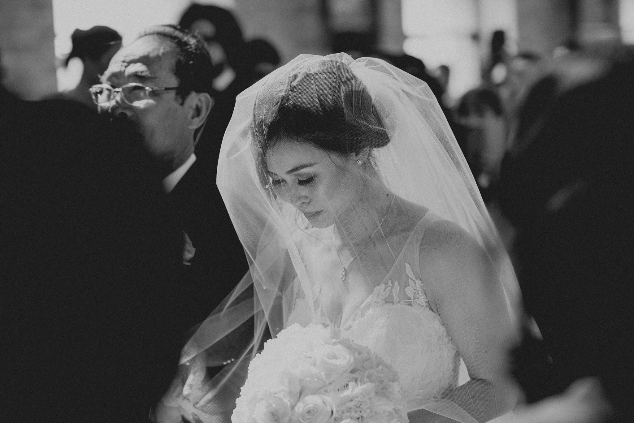 Asian bride walks down the aisle at her wedding covered by a veil