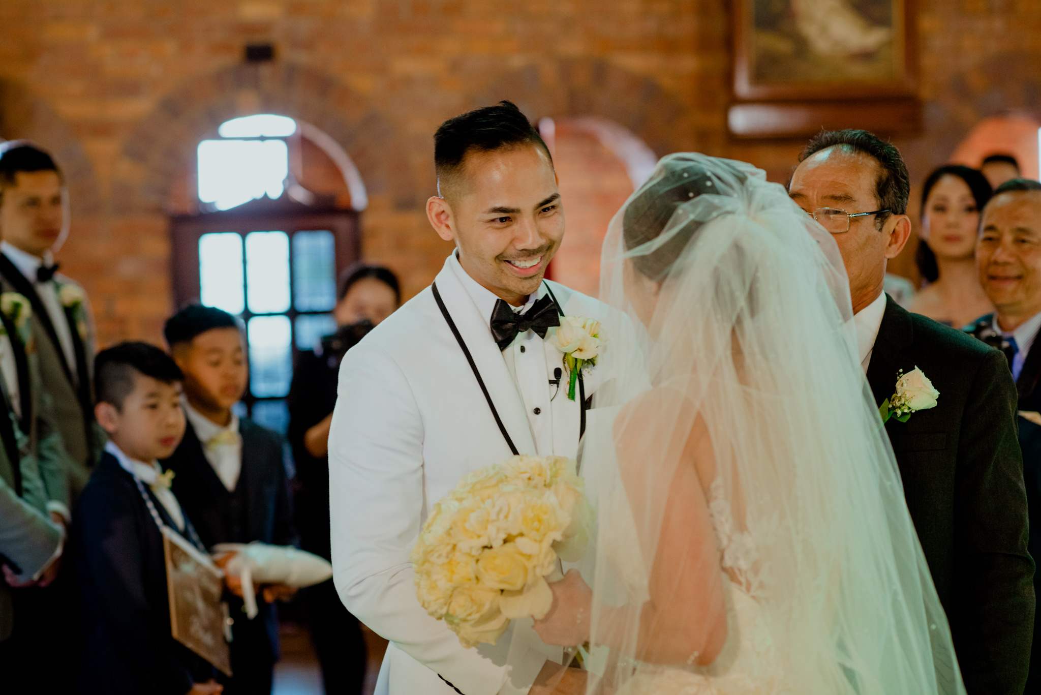 Asian groom smiles as he receives his bride