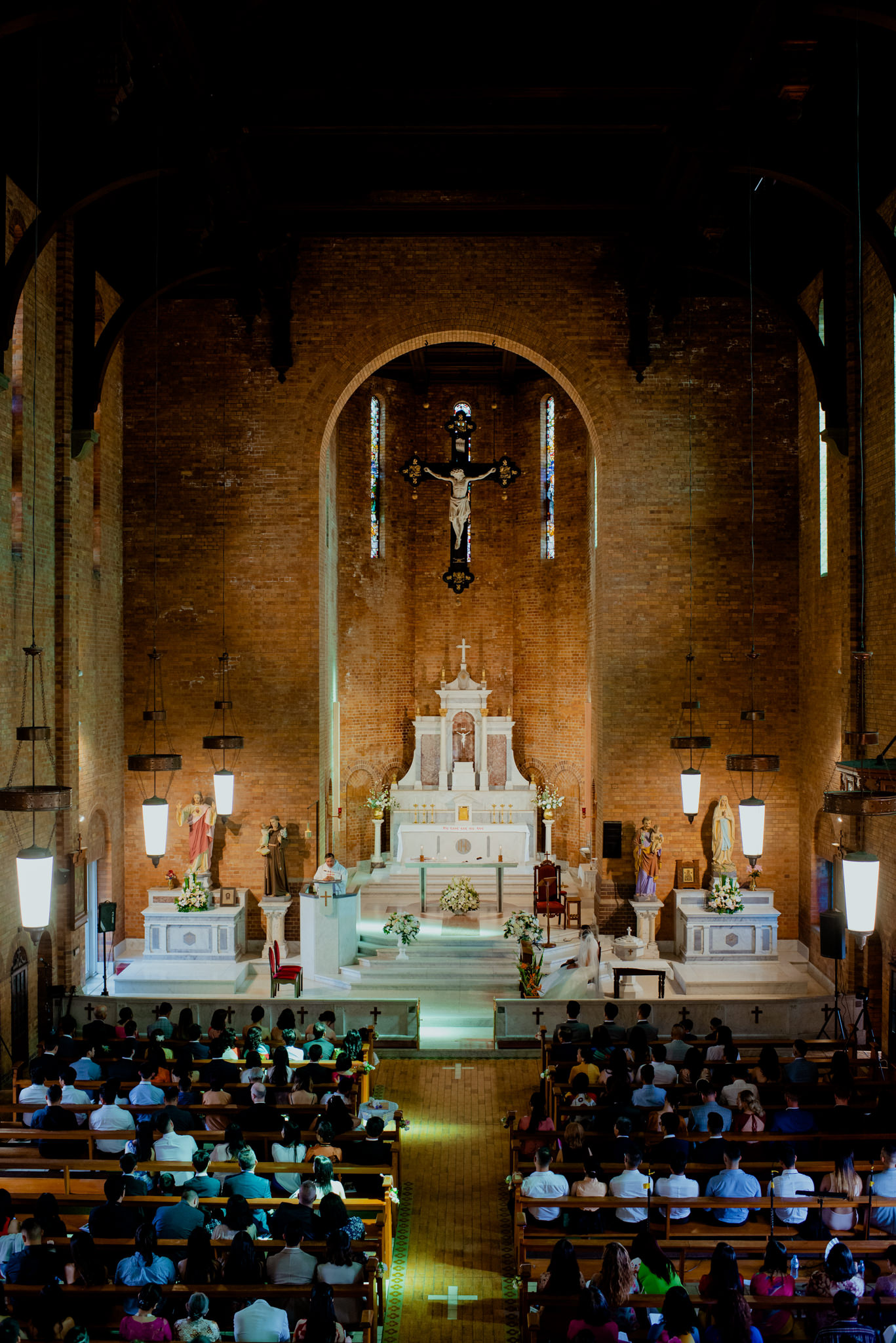 The interior of an old brick Catholic church during a wedding ceremony
