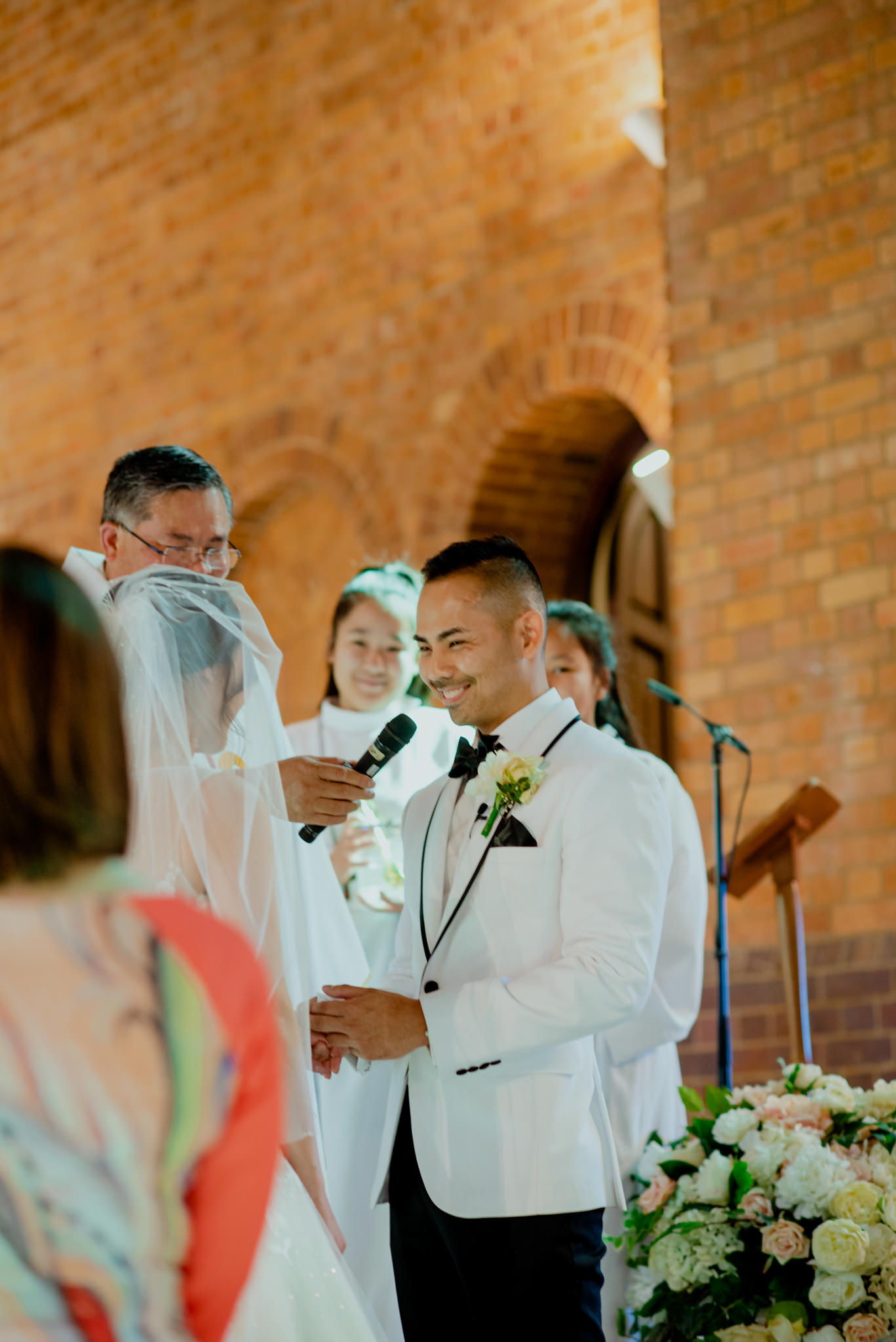 Vietnamese groom smiles as he delivers his vows