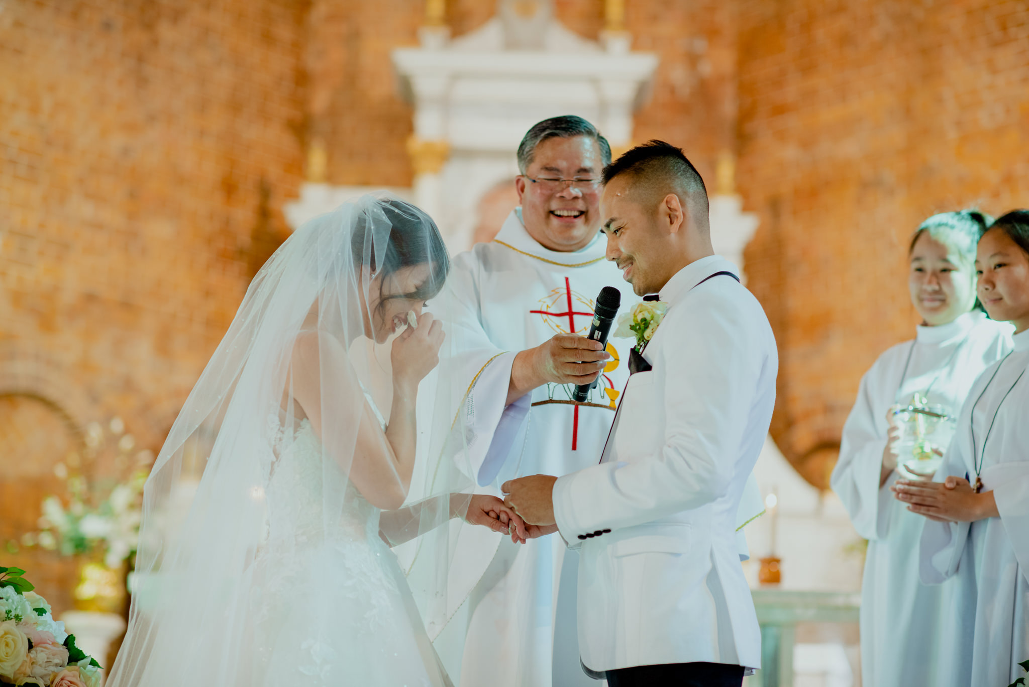 Asian groom laughs and asian bride cries as they exchange rings during a Catholic wedding ceremony