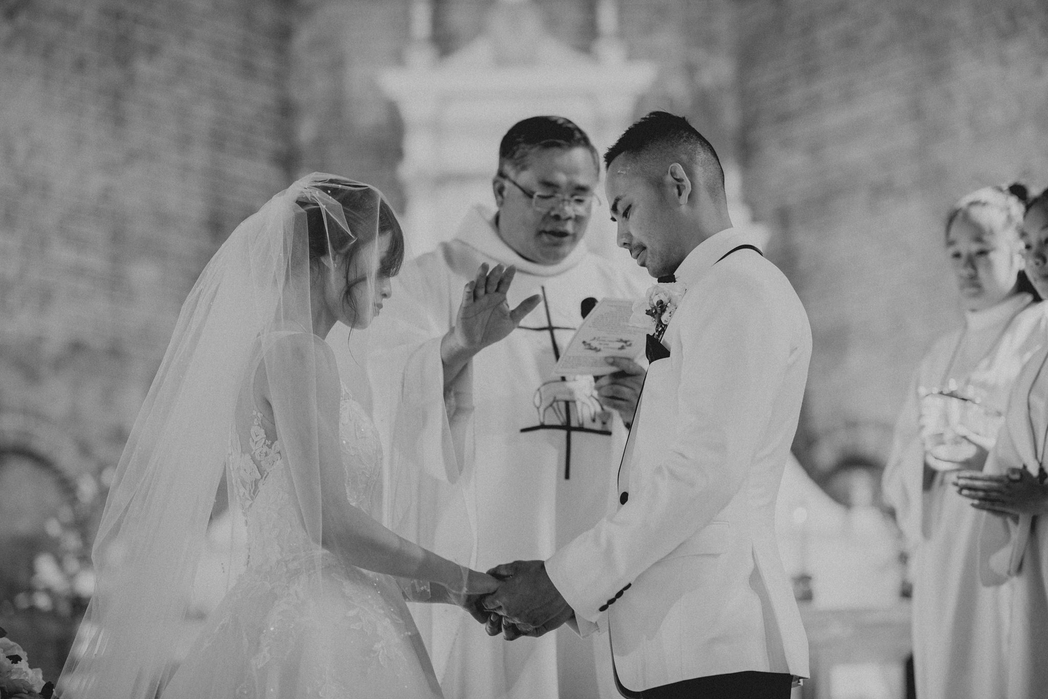A Catholic priest prays for an Asian couple getting married