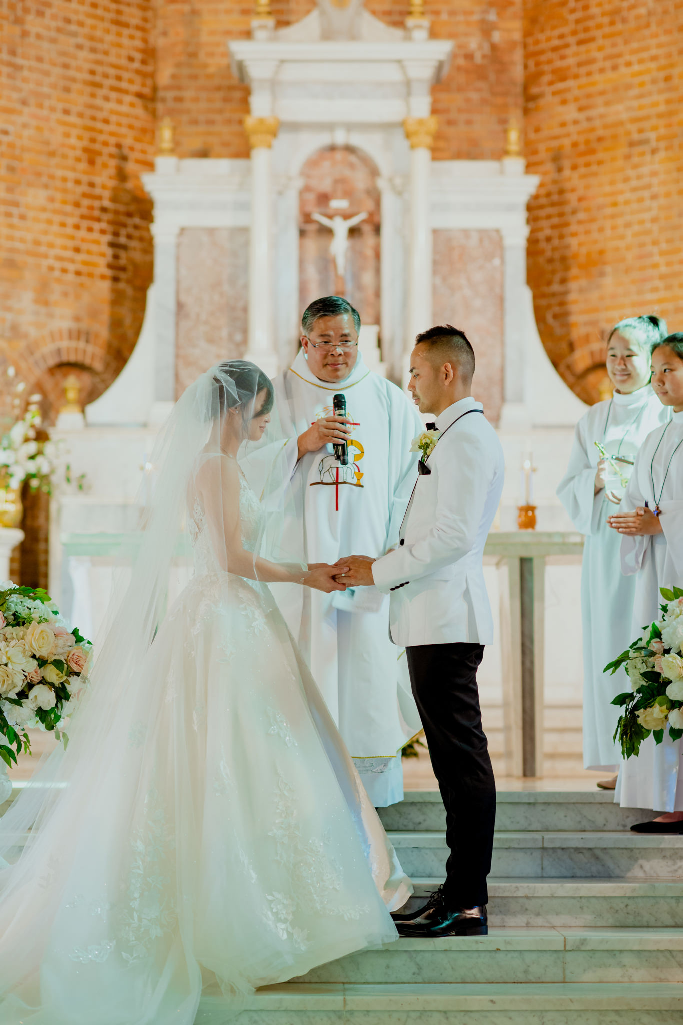 A Vietnamese couple getting married stand at the altar in front of a priest