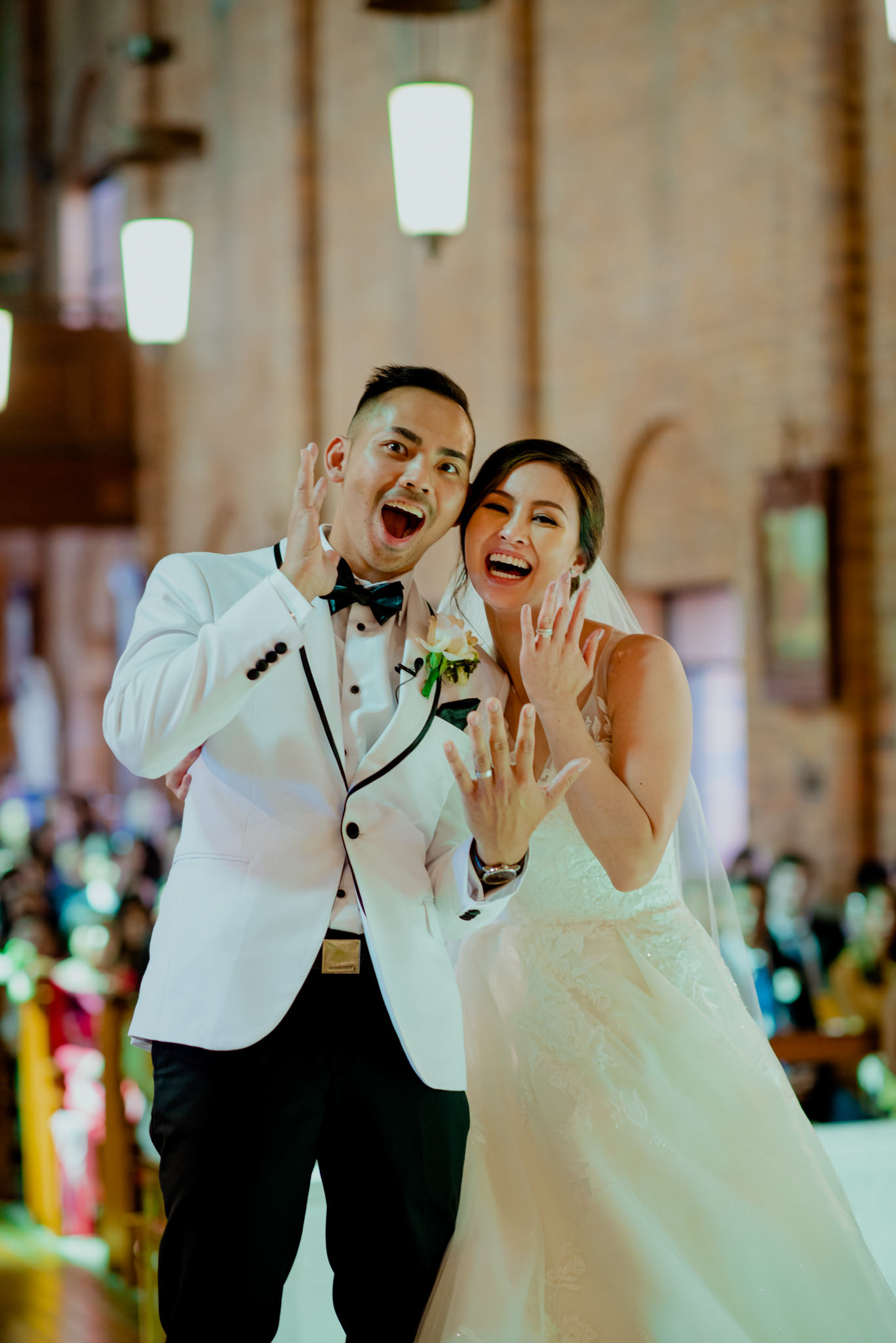 A bride and groom laugh and look shocked as they show off their wedding rings
