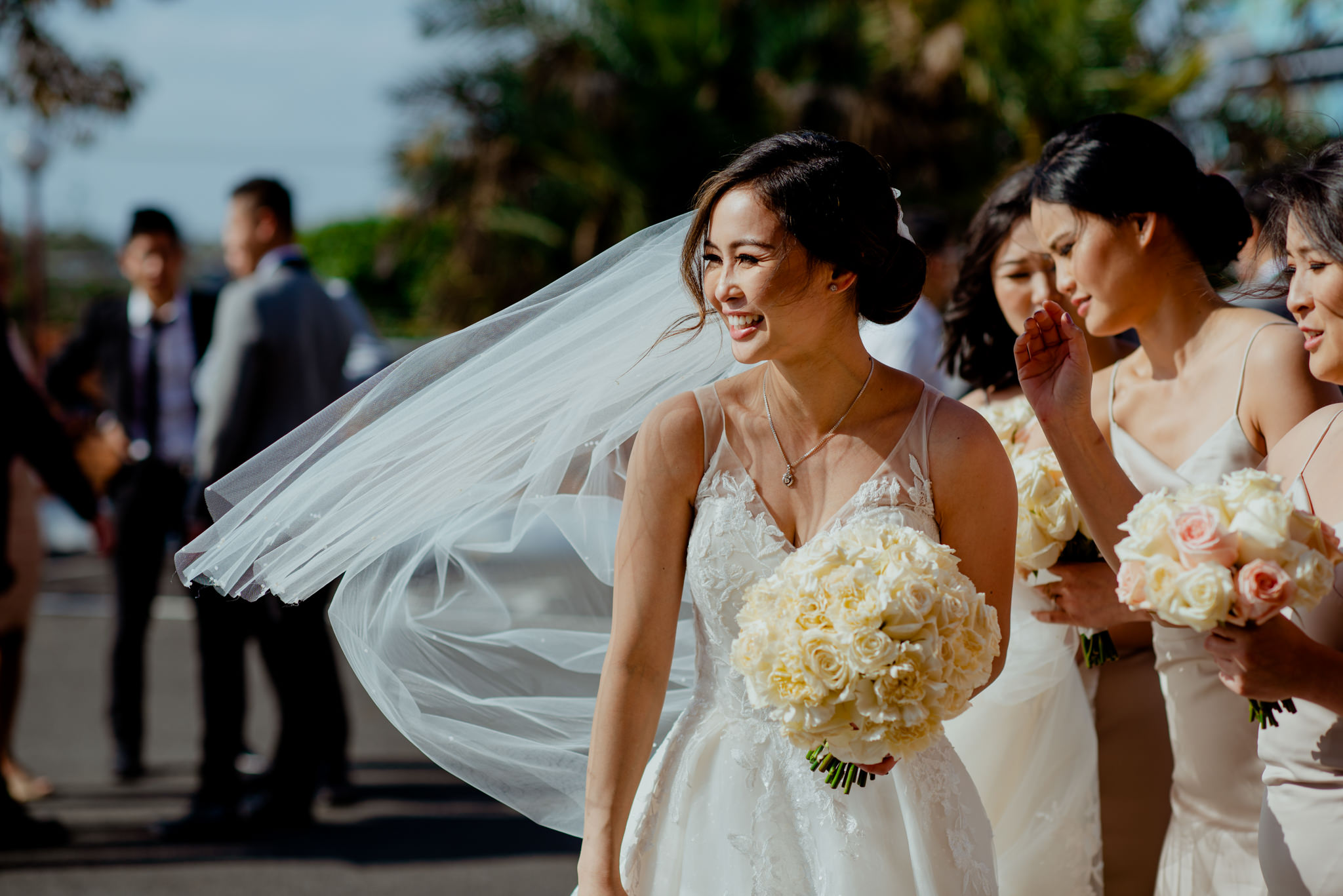 An Asian bride smiles and laughs as her wedding veil flows in the wind