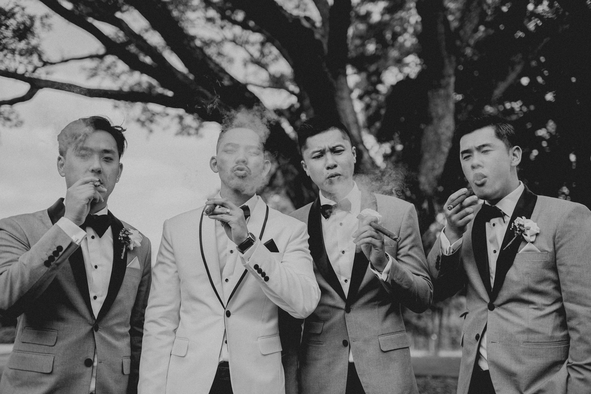Four men in tuxedos smoke cigars and blow smoke in a line