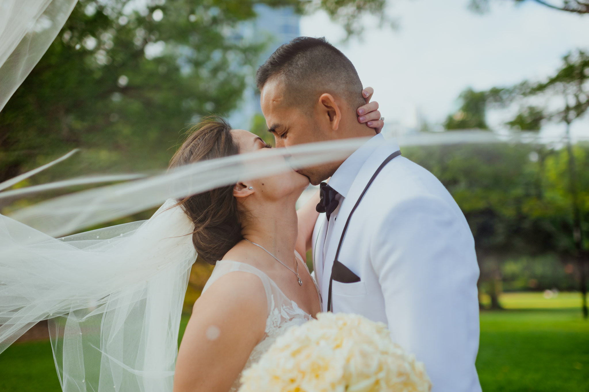An Asian couple kiss as the bride's veil flows in the wind in front of the camera