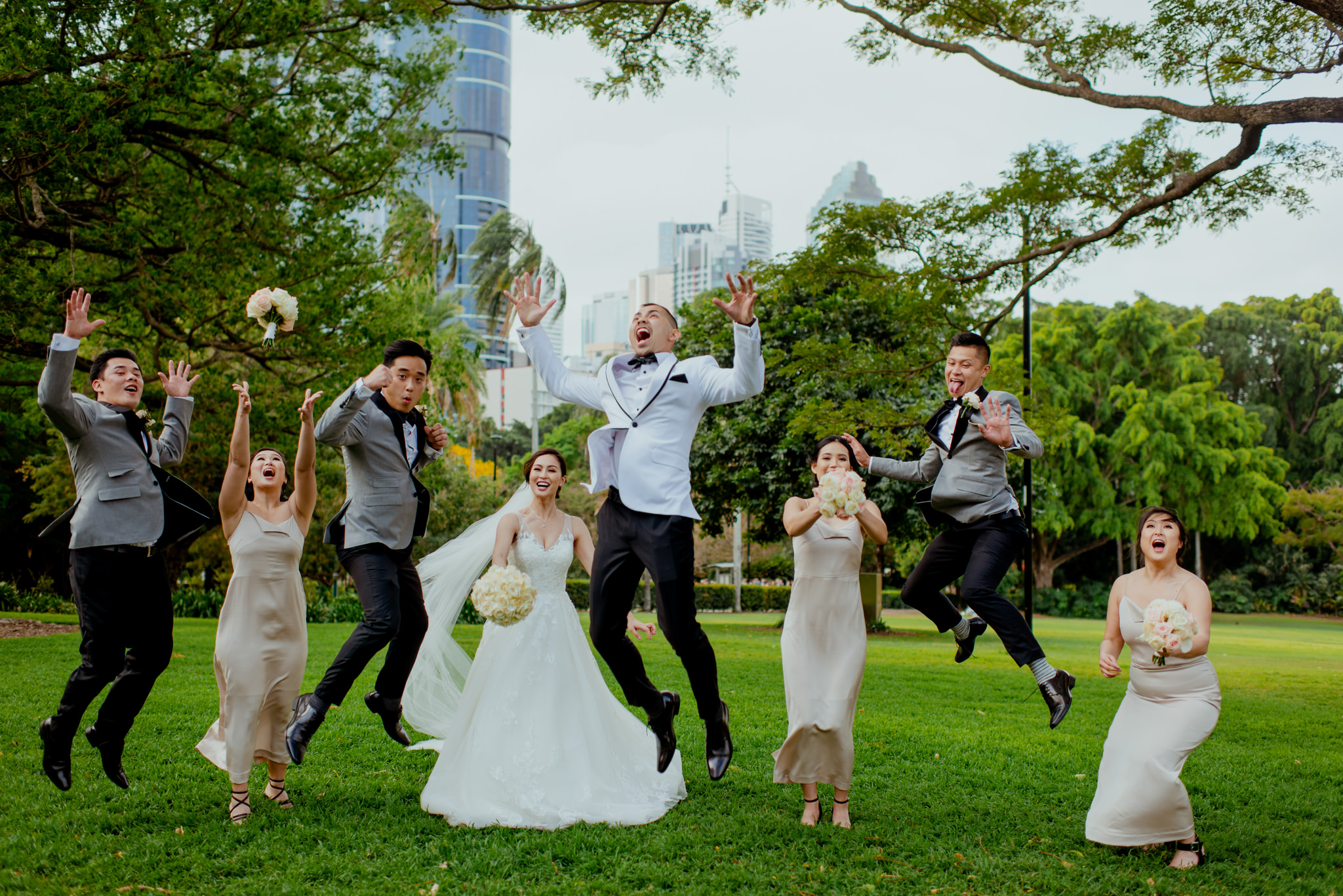 A wedding party jump and throw their bouquets in the air in a luscious green garden