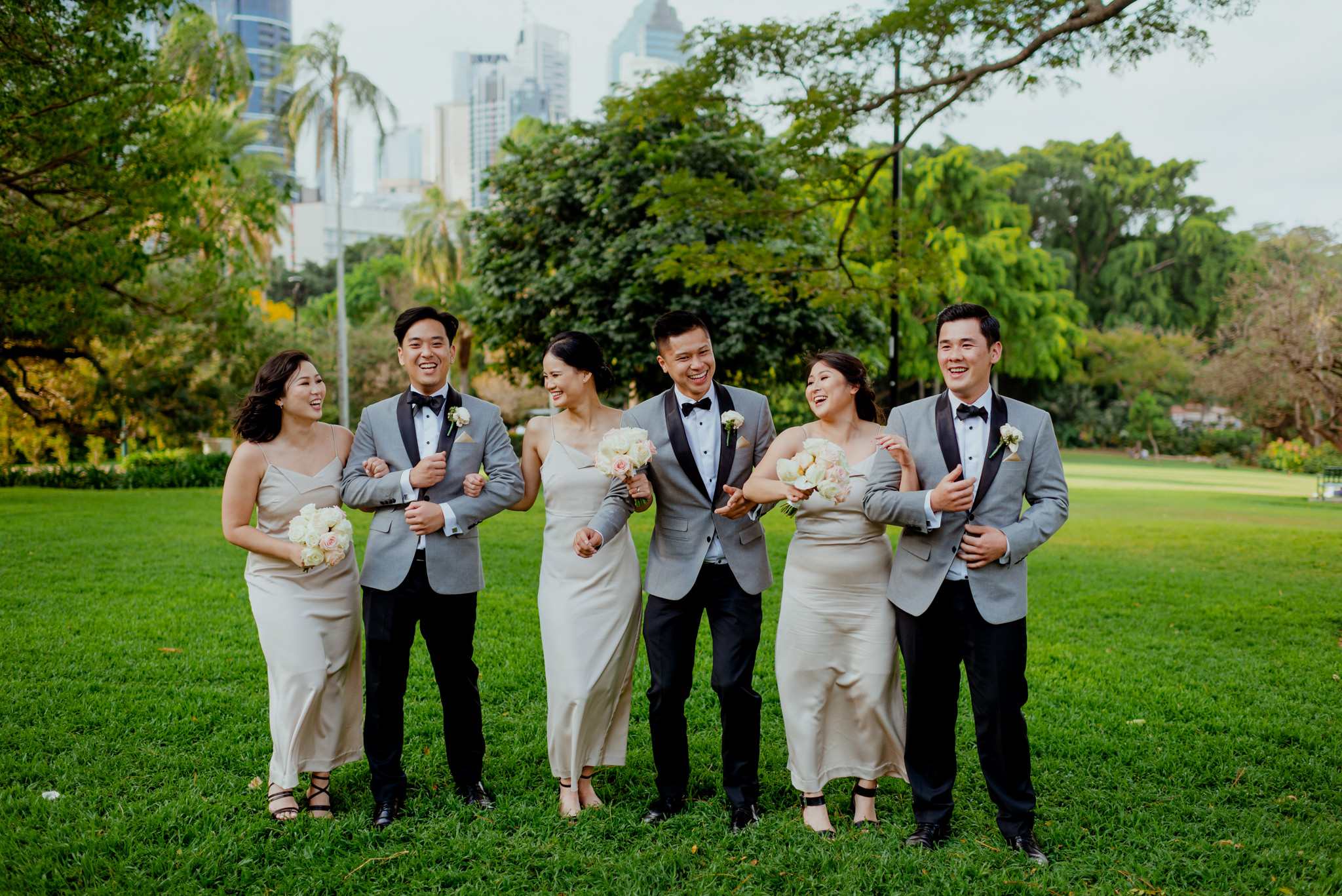 Three groomsmen and three bridesmaids link arms and laugh together