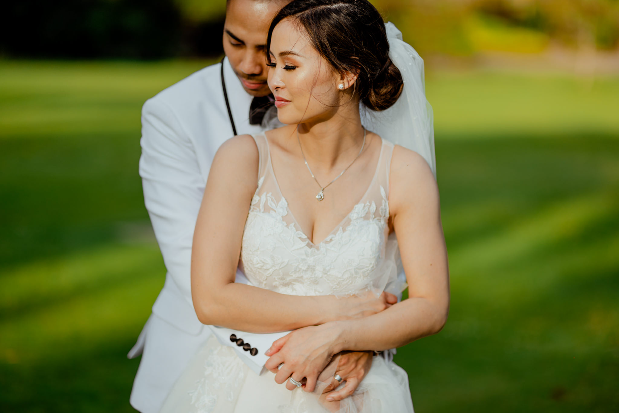 An Asian couple hug each other intimately in their wedding outfits