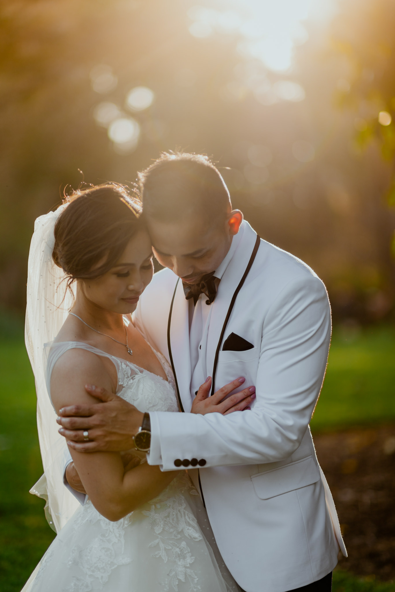 Groom embraces his wife emotionally in golden afternoon light
