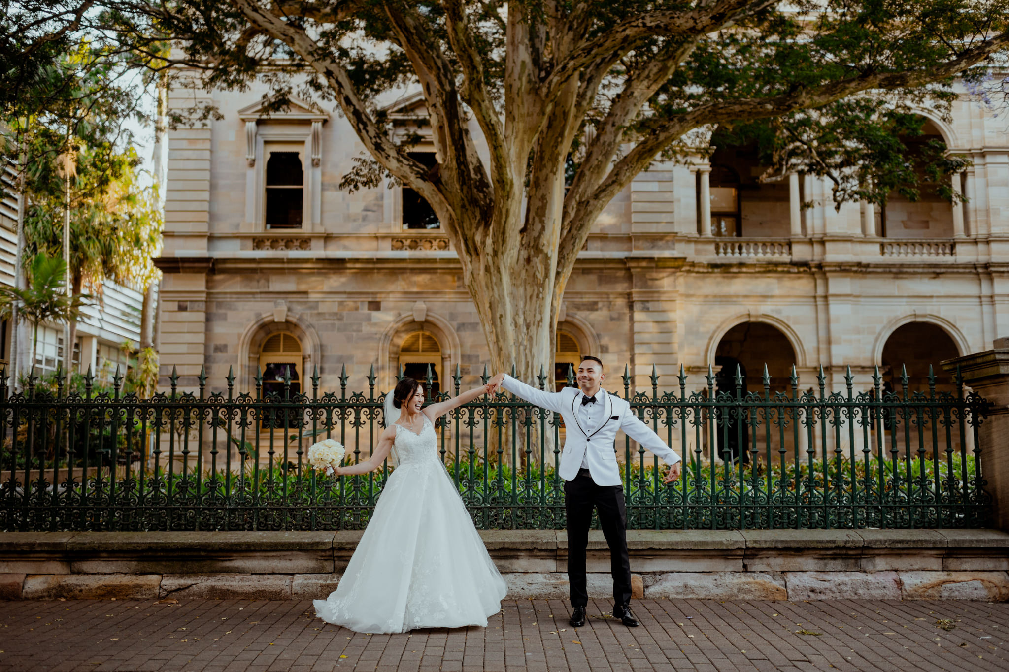 A Vietnamese wedding couple swing their arms playfully in front of a fenced sandstone building