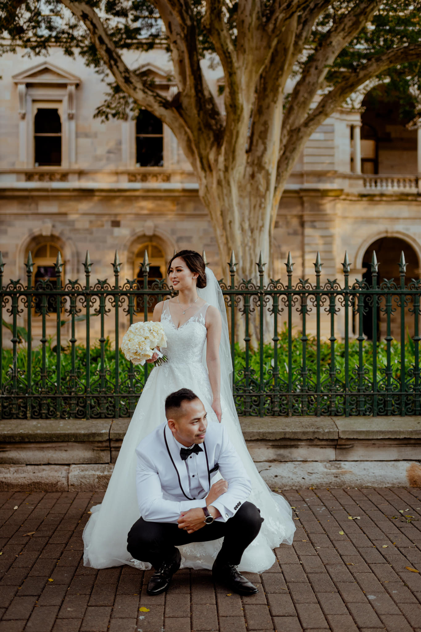 A Vietnamese wedding couple pose seriously in front of a fenced sandstone building