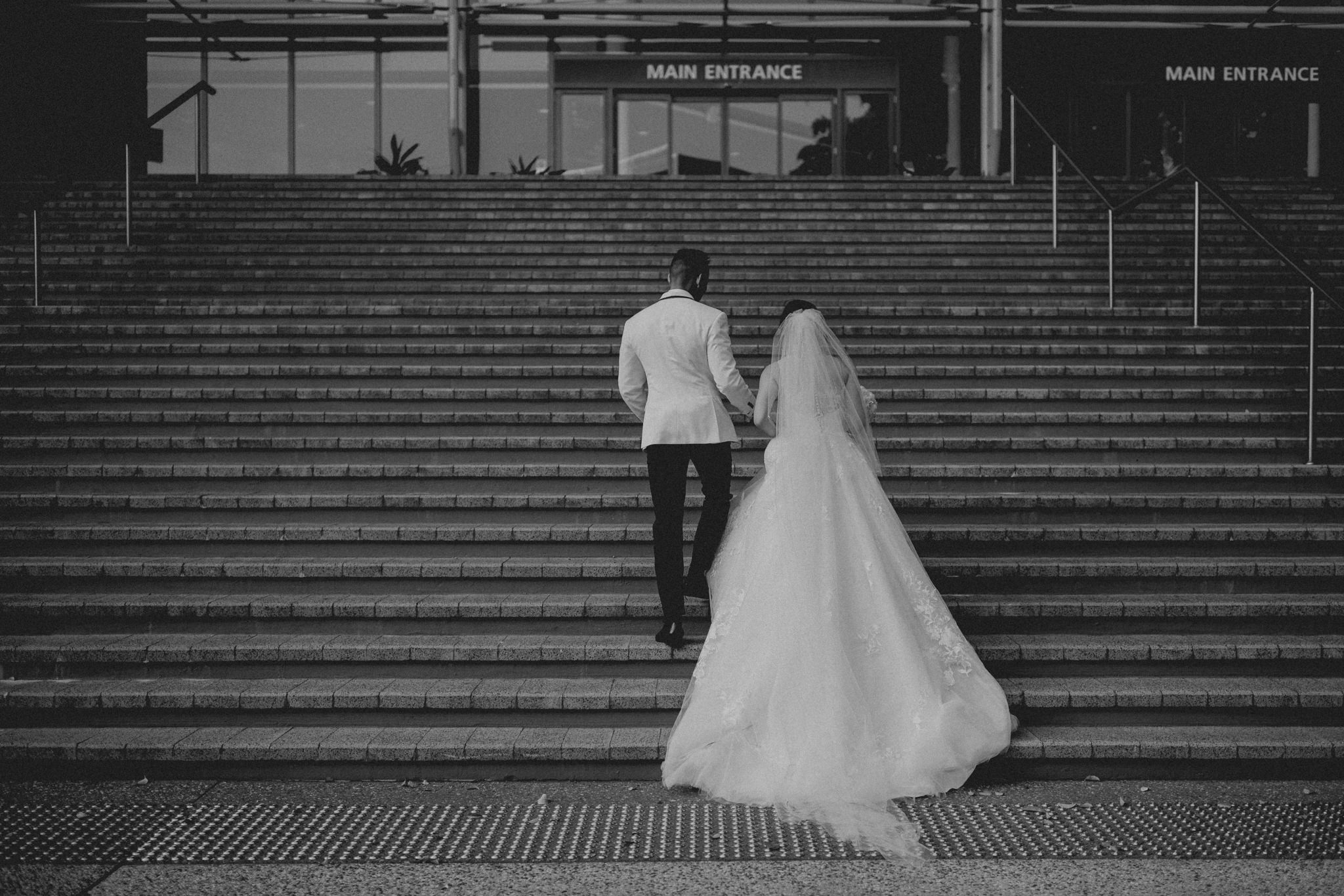 A bride and groom walk up a large staircase leading to doors