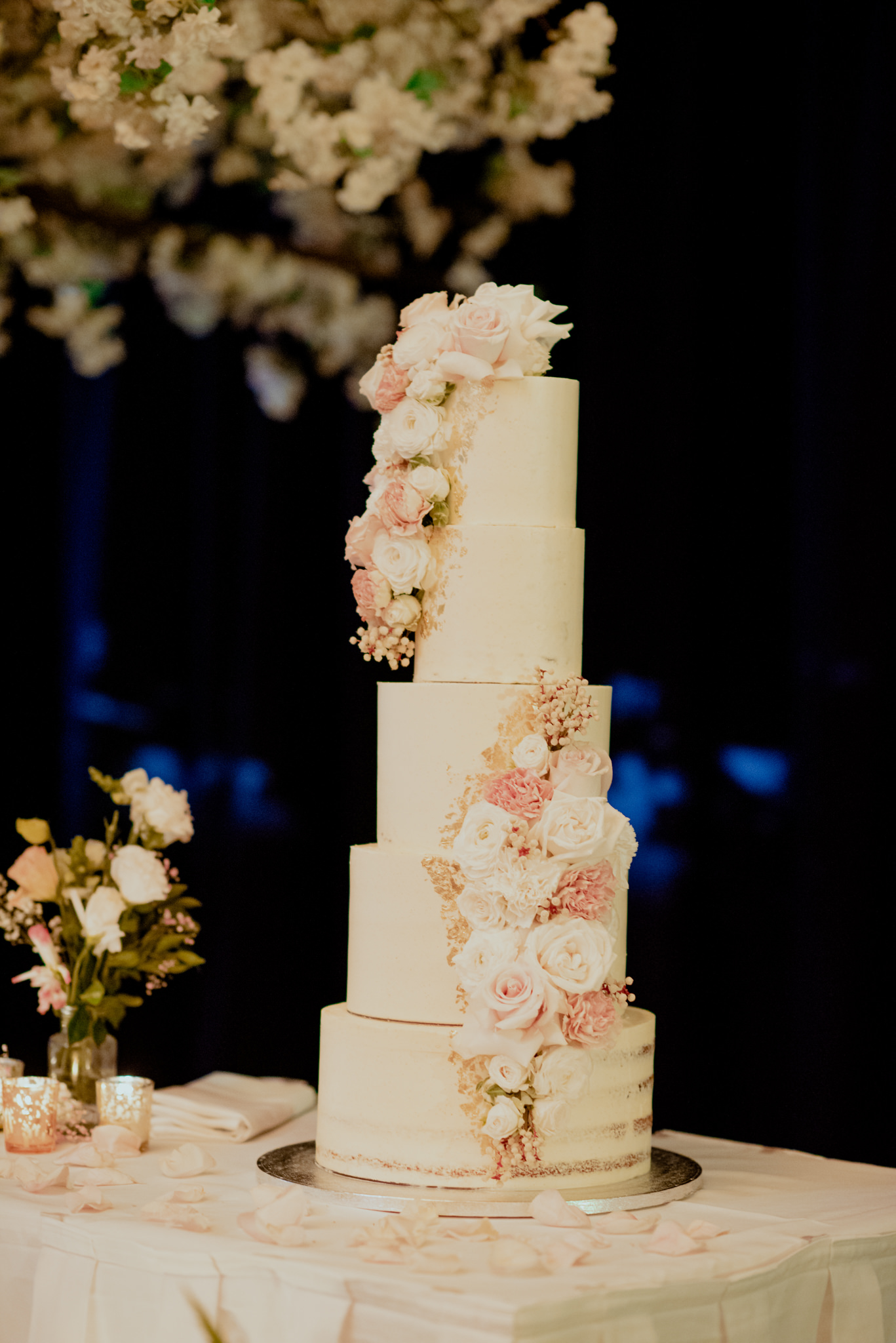 A five tiered white wedding cake with flowers on a table