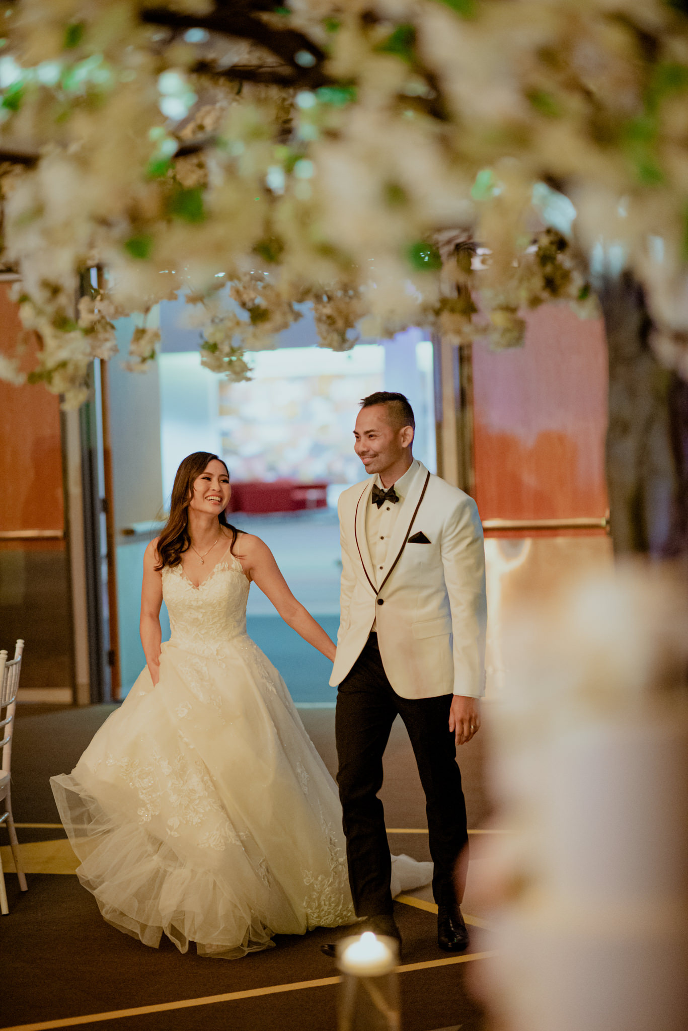 Bride and groom walk underneath an indoor blossom tree decoration