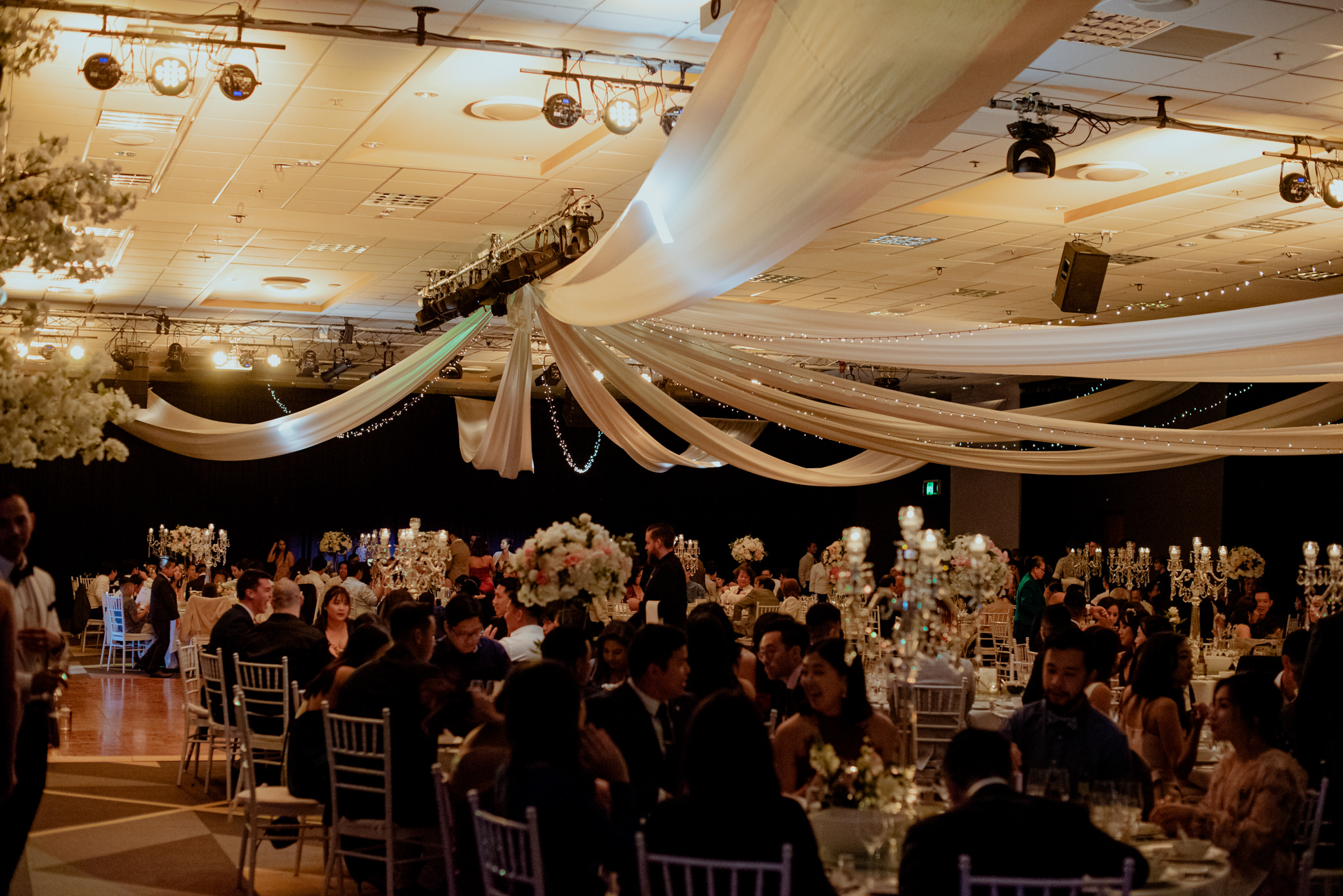 A large banquet hall filled with wedding guests at a convention centre