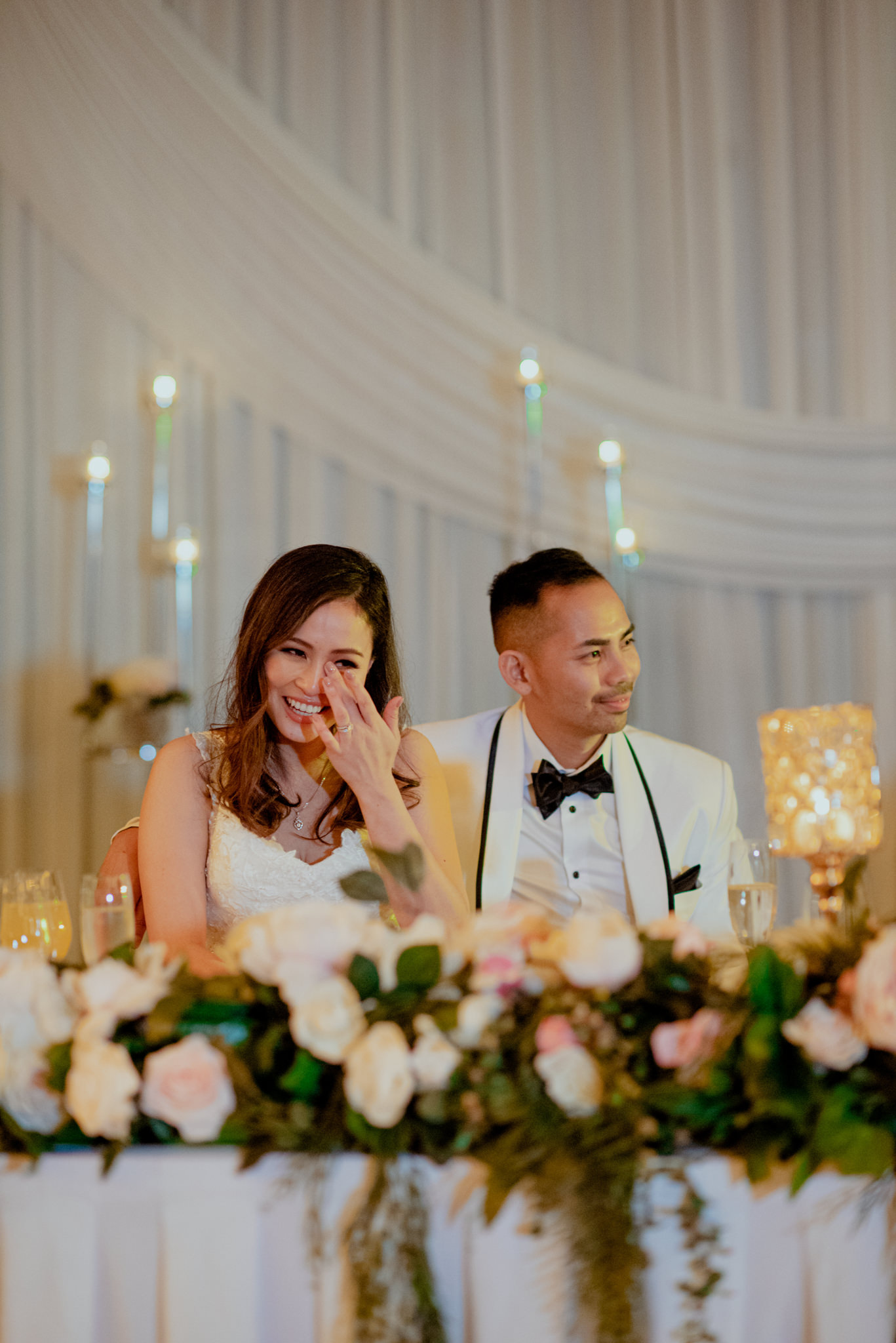 An Asian bride sits at a table and wipes away a tear with her husband wrapping her arm around her shoulder