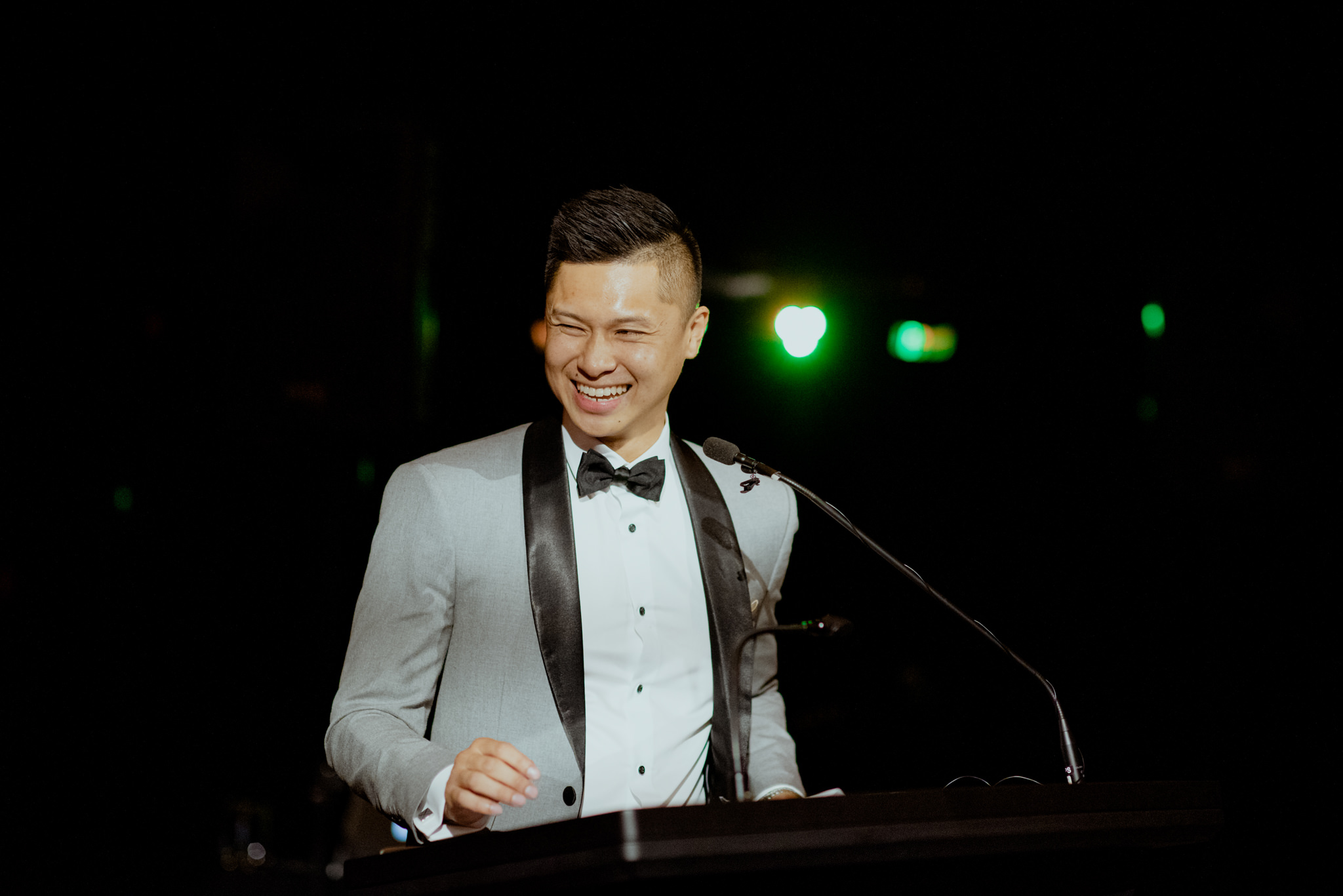 An Asian man in a tuxedo stands at a podium and laughs