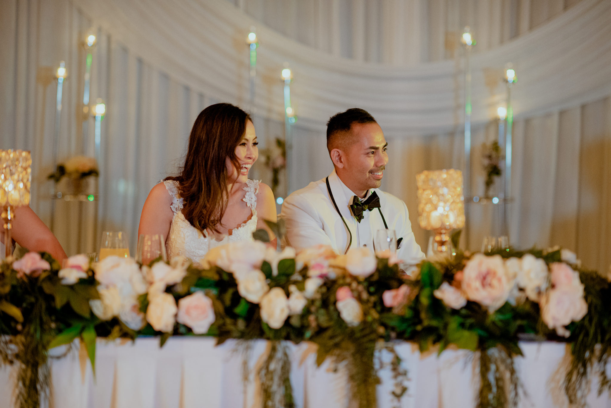 Newlyweds sit at their bridal table and laugh at speeches