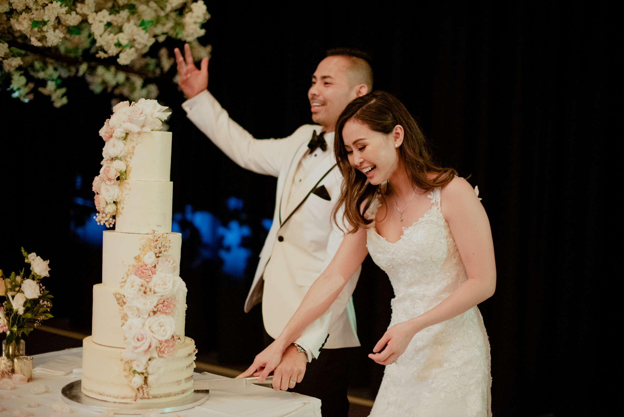 Newlyweds cut into their five tiered wedding cake and laugh