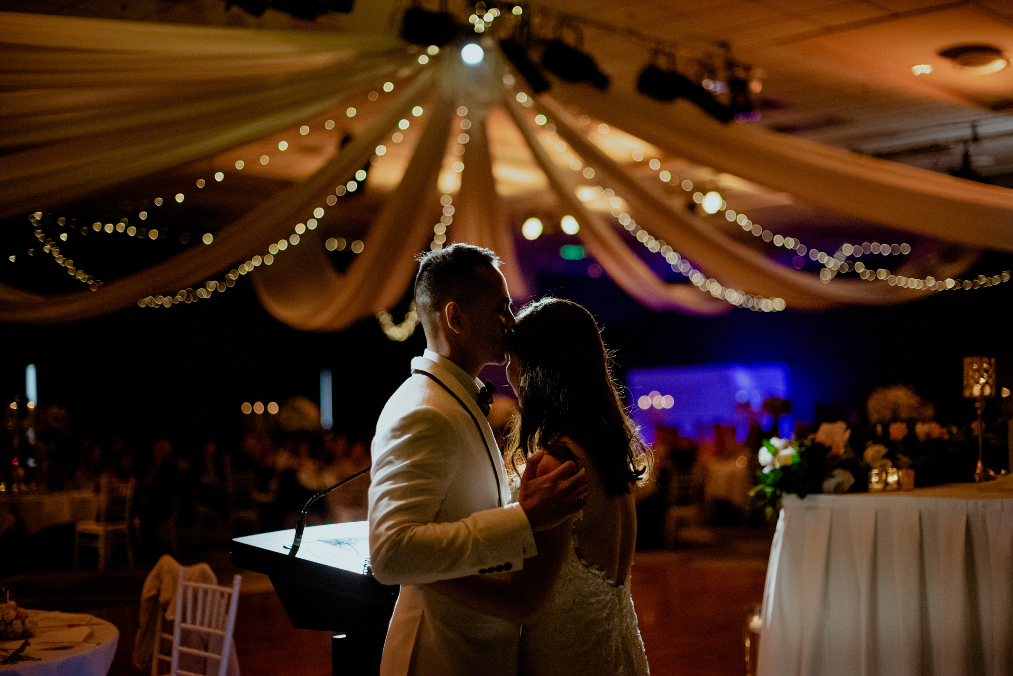A groom kisses his bride's forehead in front of a spotlight at their reception