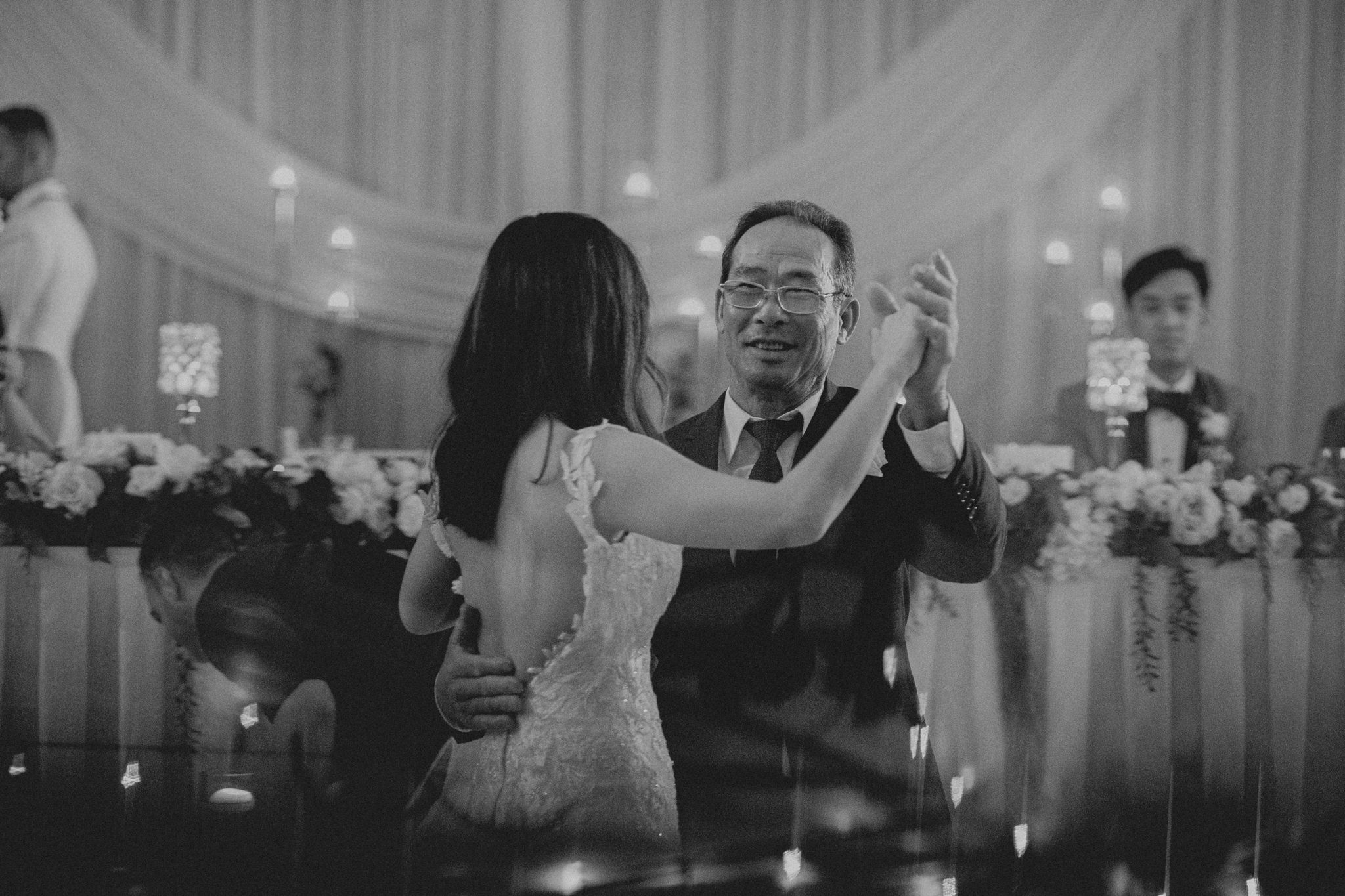 An elderly asian man dances with his daughter at her wedding