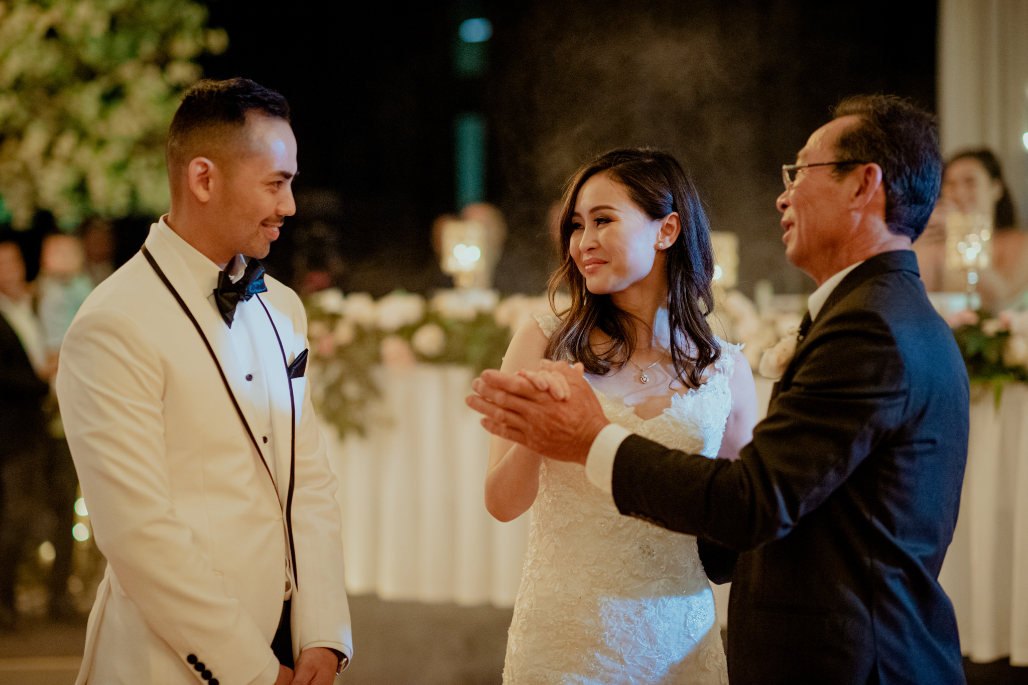 A groom approaches his bride who is dancing with her father at their wedding